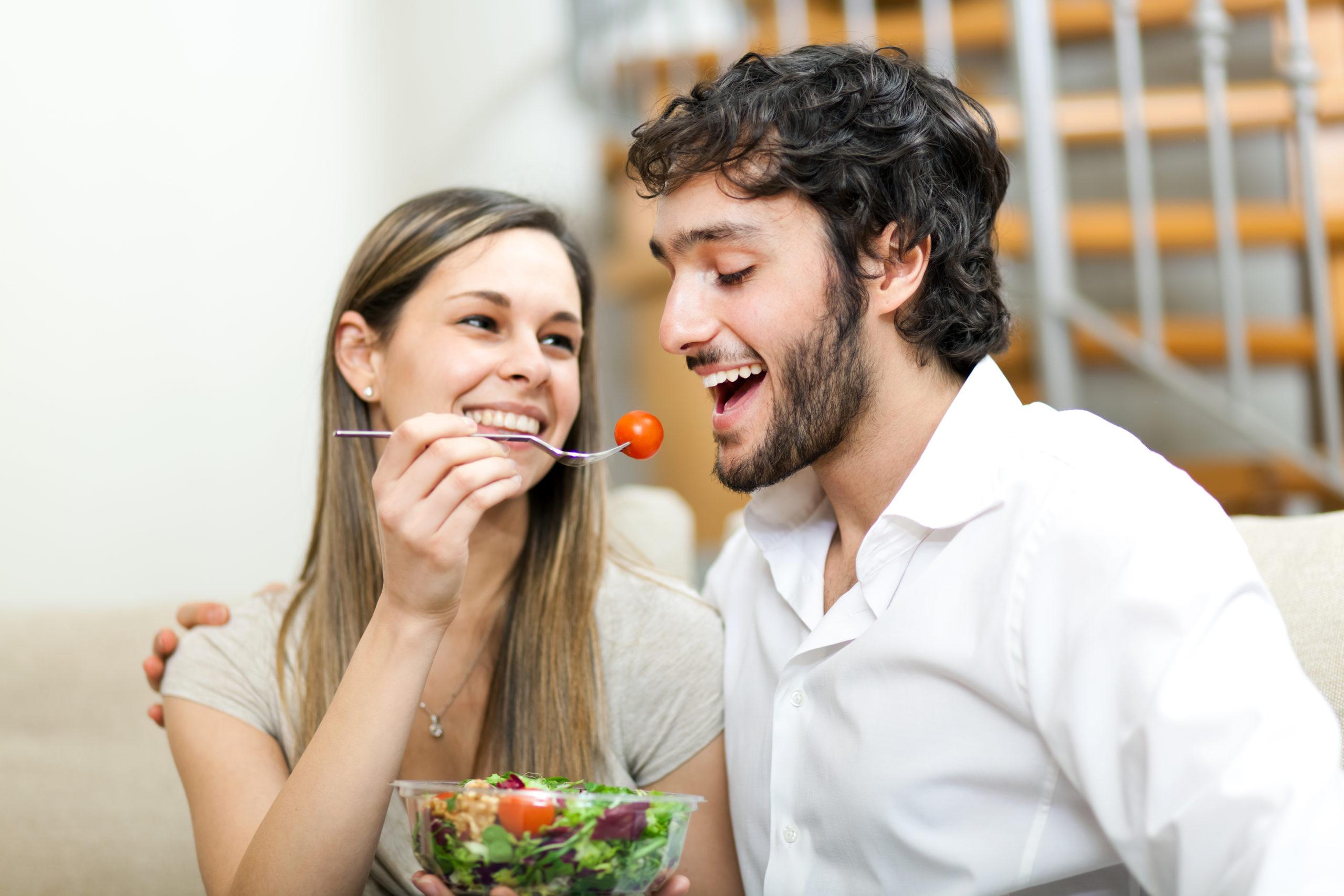 男性に食べ物を食べさせる女性の画像です