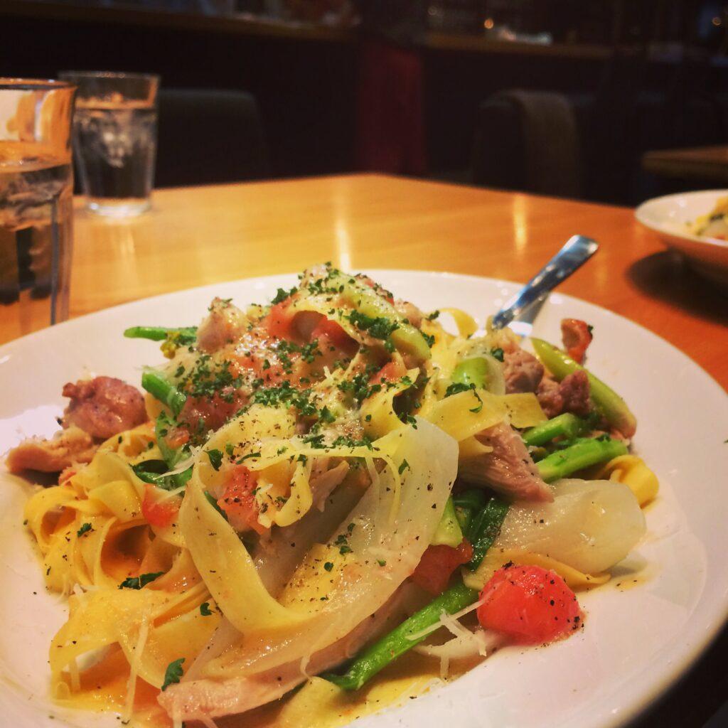 サラダチキンとアスパラ、新玉ねぎフレッシュトマトのアンチョビ風味タリアッテッレの画像です。