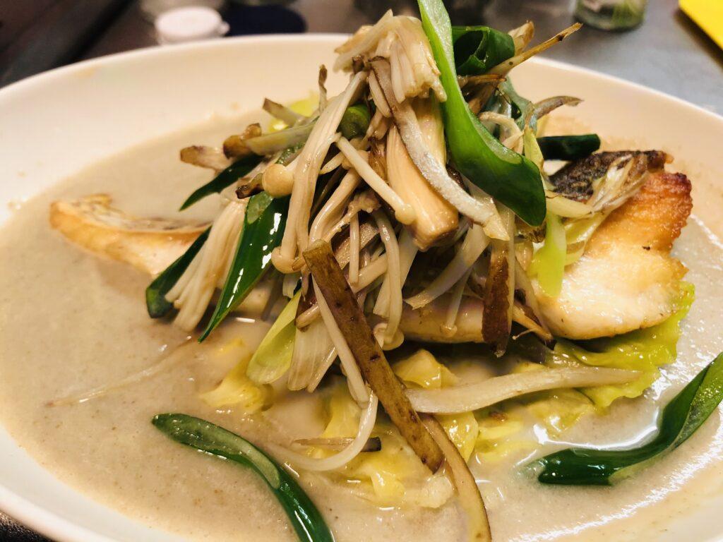 ゴボウのスープにアンチョビキャベツ、真鯛のポワレ、ソテーした九条ネギ、えのき、新ごぼうのささがきをのせました。