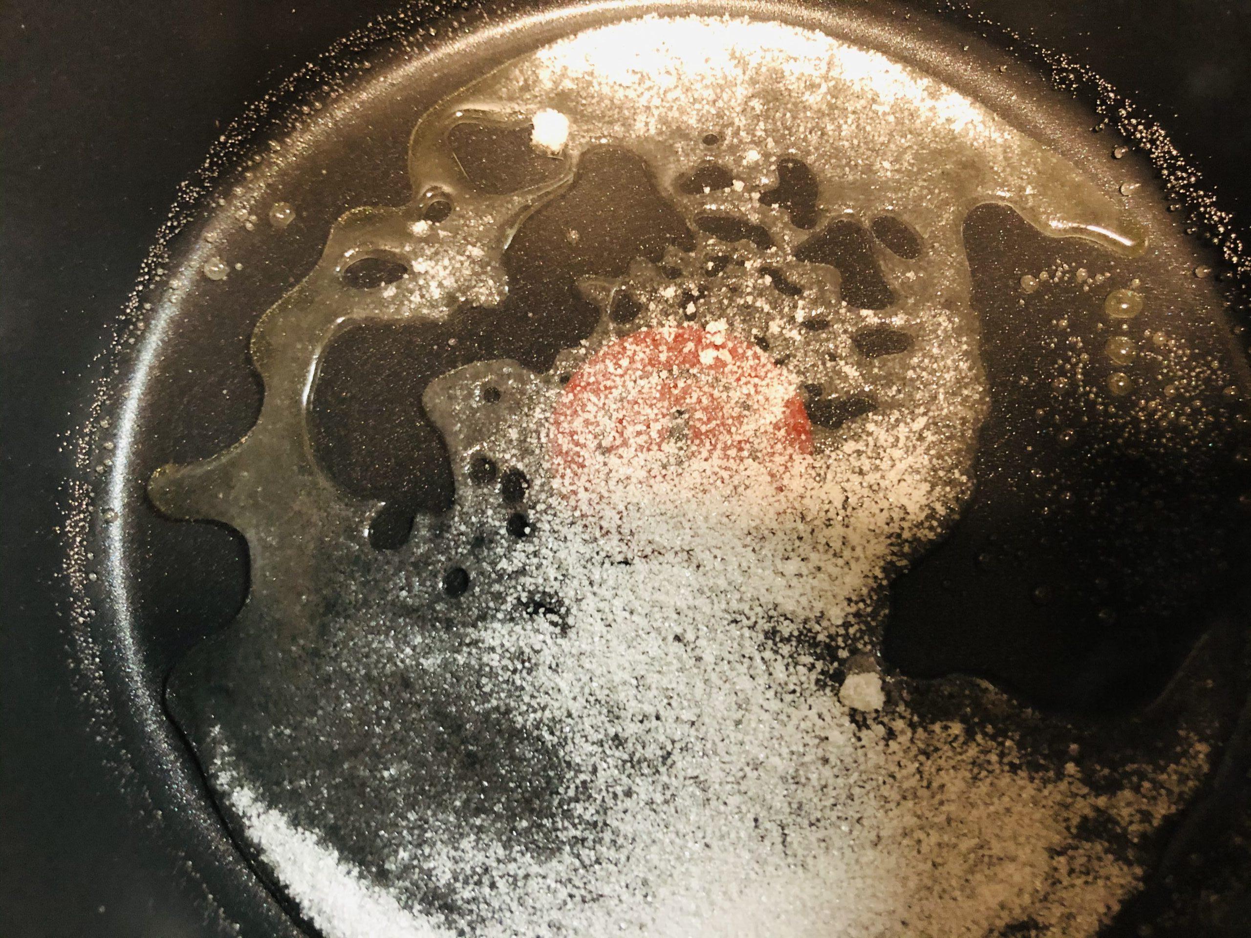 キャラメル用のグラニュー糖を火にかけて徐々に溶けてきた様子の画像です。