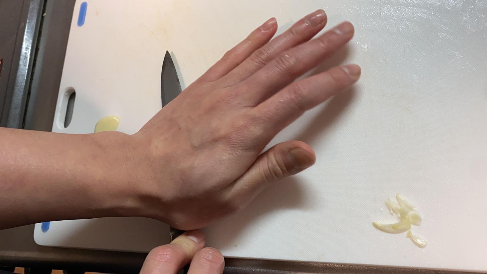 芽を取り除いたニンニクを包丁の腹で叩き潰す様子の画像です