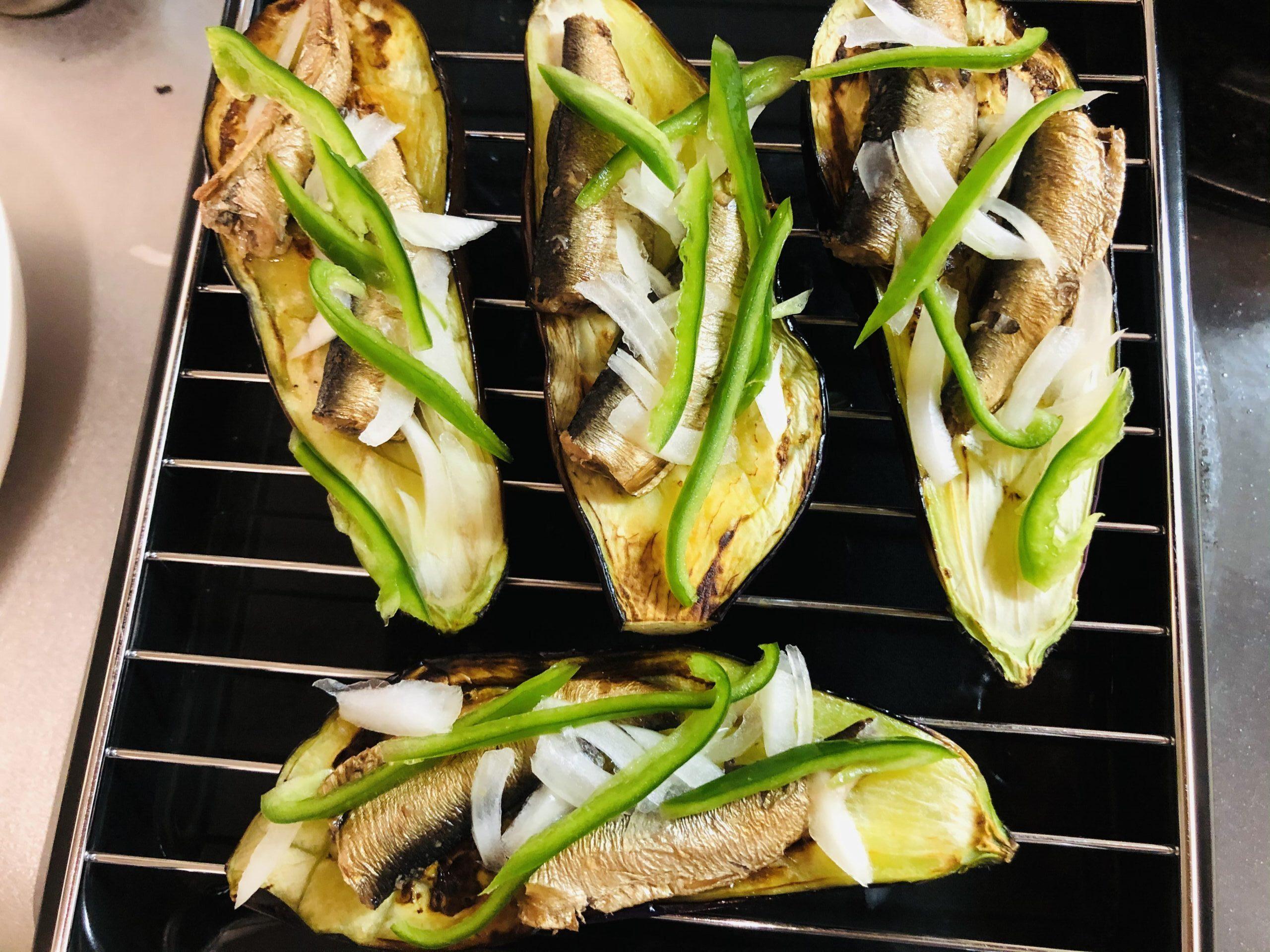 魚焼きグリルに先程焼いたナスをのせ、スモークオイルサーディン、玉ねぎスライス、細切りピーマンを載せた様子の画像です
