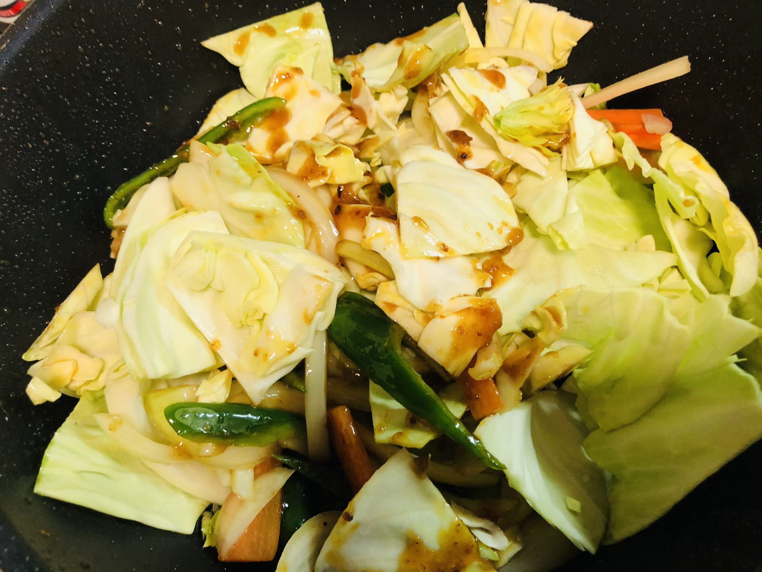 野菜を入れ合わせ調味料と絡めて炒めている様子の画像です