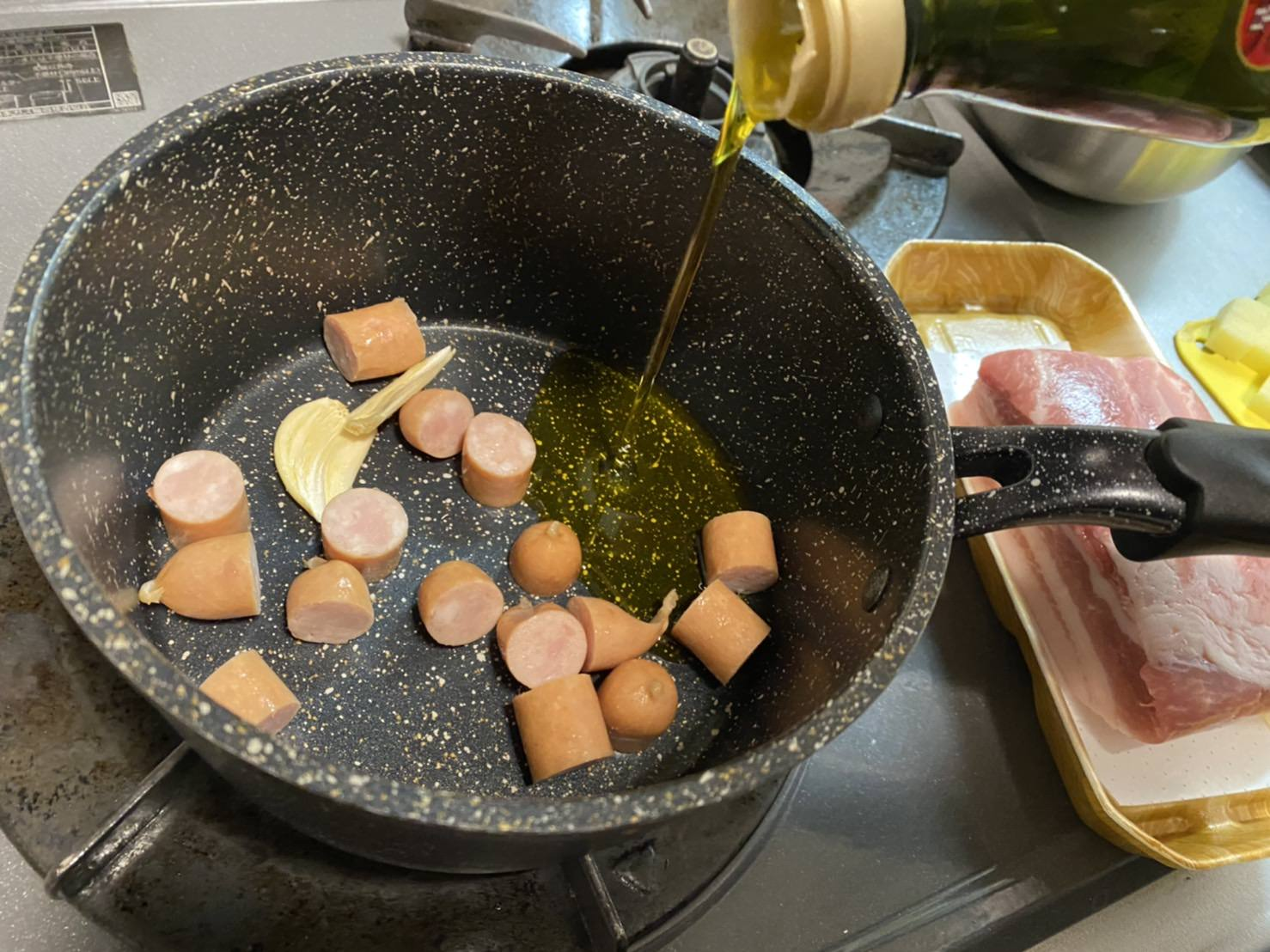 潰したにんにくとウインナーを鍋に入れ、オリーブオイルを注ぐ様子の画像です。