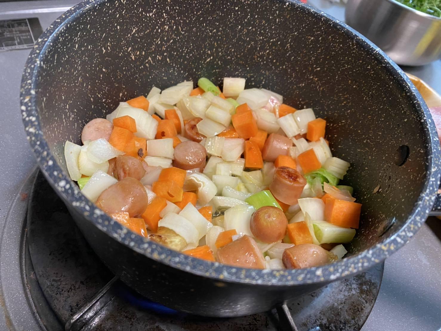 玉ねぎ、ニンジン、セロリ、ネギの白い部分を鍋に入れた画像です。