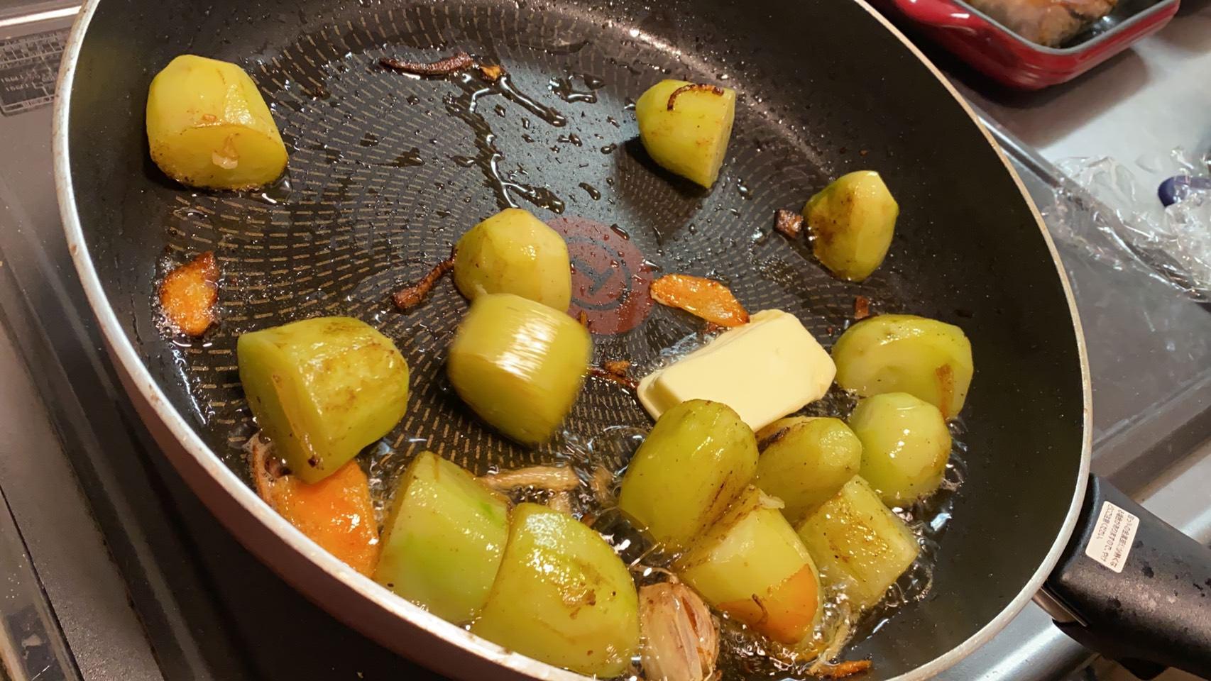 揚げ焼きにしたジャガイモにバターを入れた様子の画像です