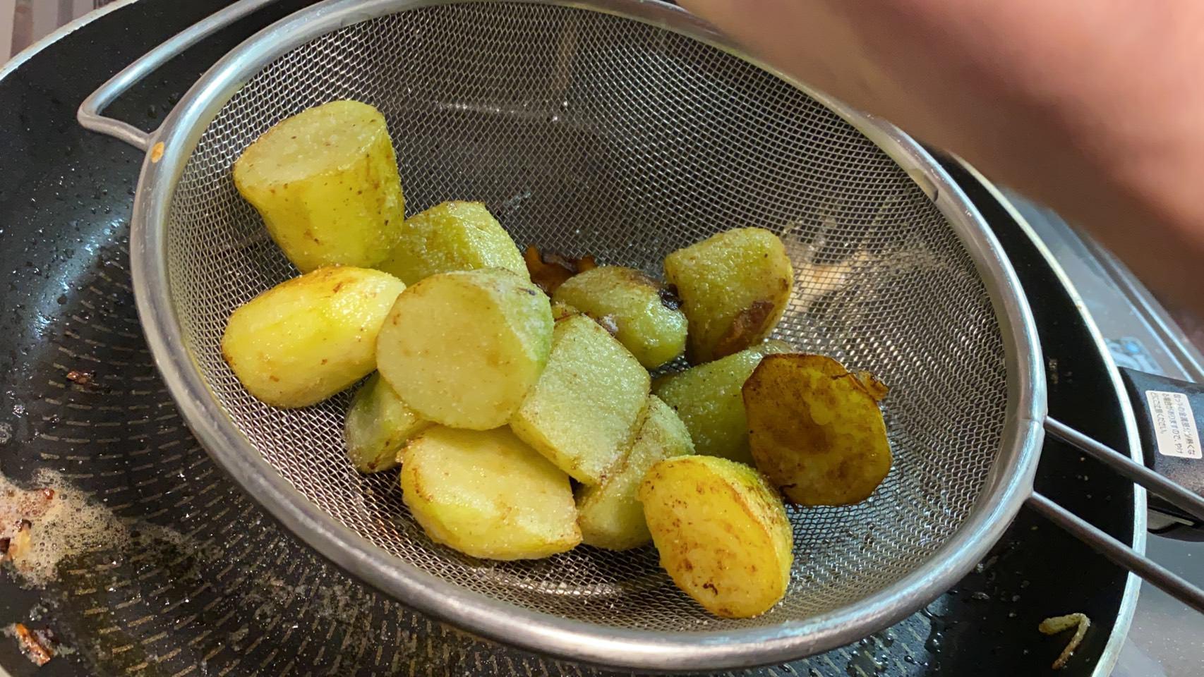 ザルに開けたジャガイモに塩胡椒する様子の画像です