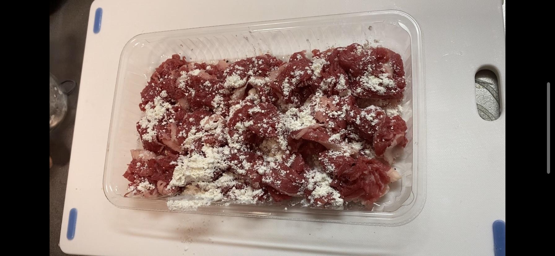 牛細切れ肉に塩コショウ、薄力粉をまぶした様子の画像です