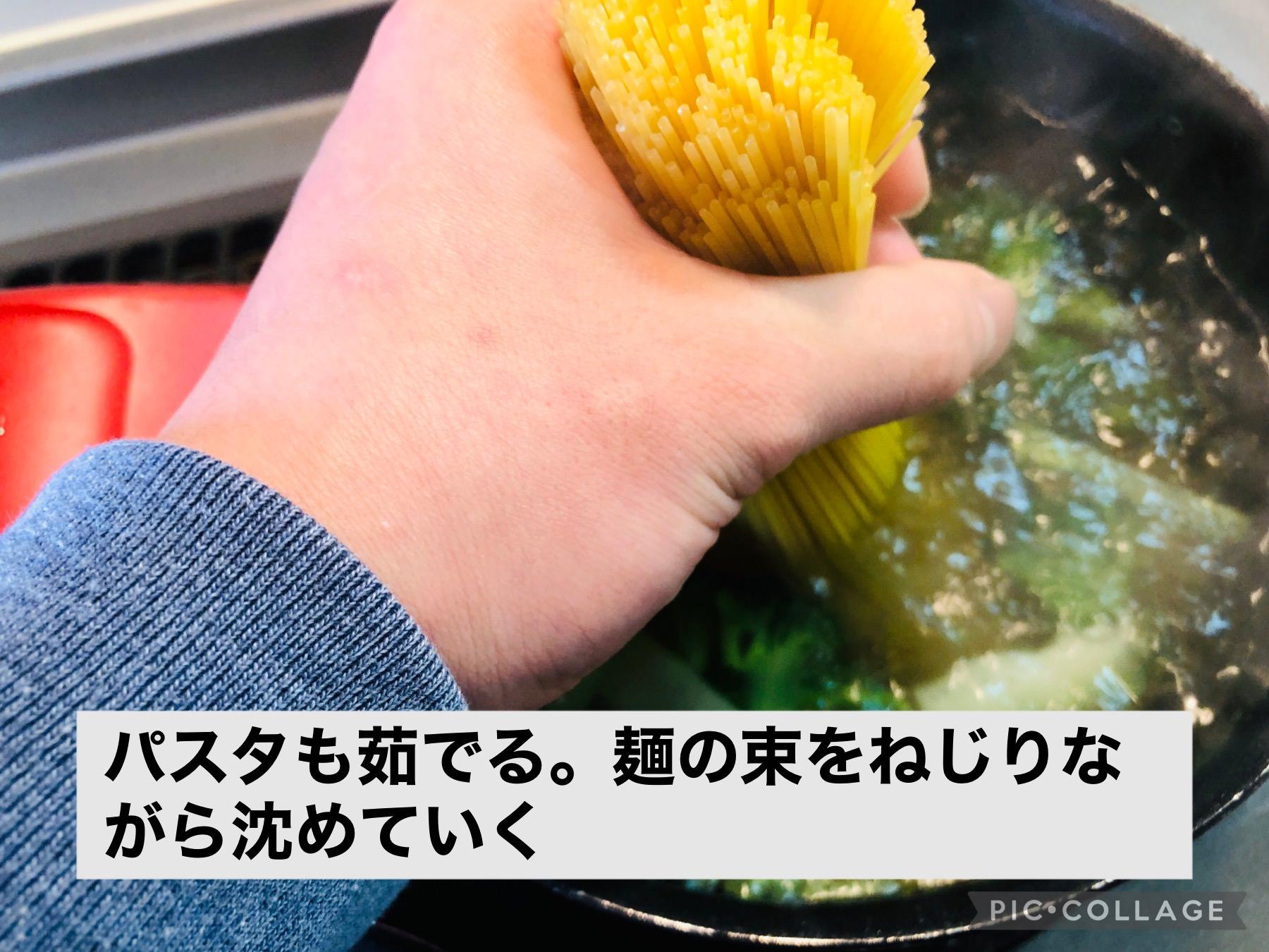 パスタの麺の束をブロッコリーを茹でている鍋にねじりながら入れている様子の画像です
