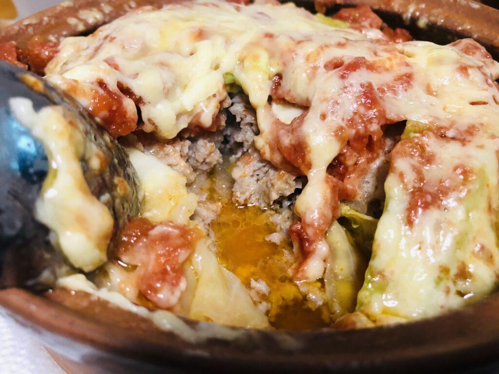 らくちんレンジで簡単包まないロールキャベツをスプーンで切り分けると肉汁とトマト、キャベツ、チーズの油分が美味しいエキスとなり溢れている様子の画像です。