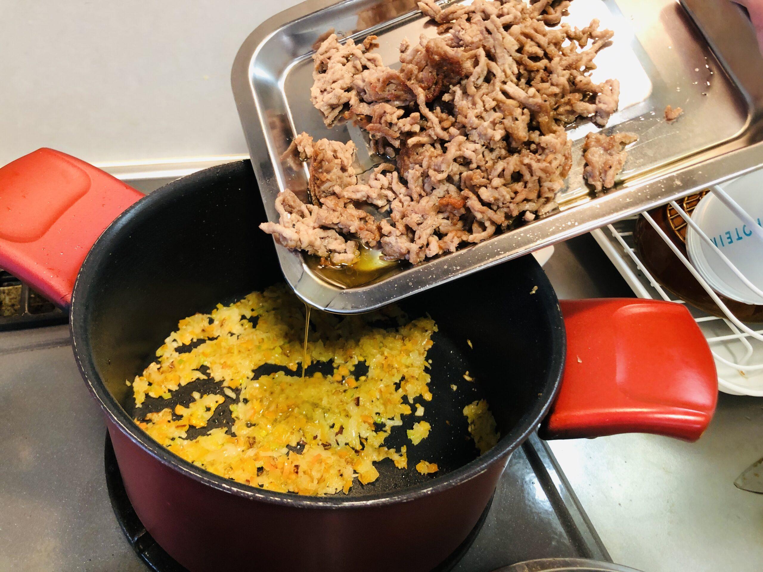 玉葱人参セロリのみじん切りを炒めている鍋にミンチ肉を戻す様子の画像です