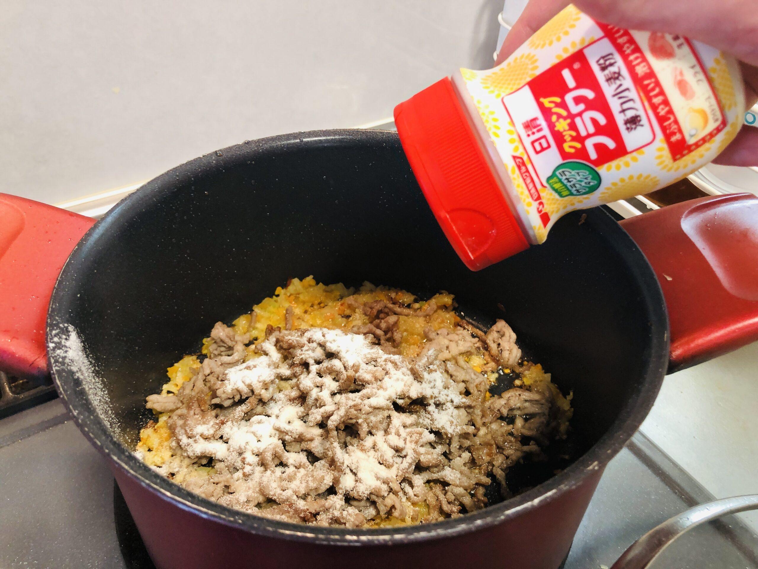 ミンチ肉を戻した鍋に、小麦粉を振り入れる様子の画像です