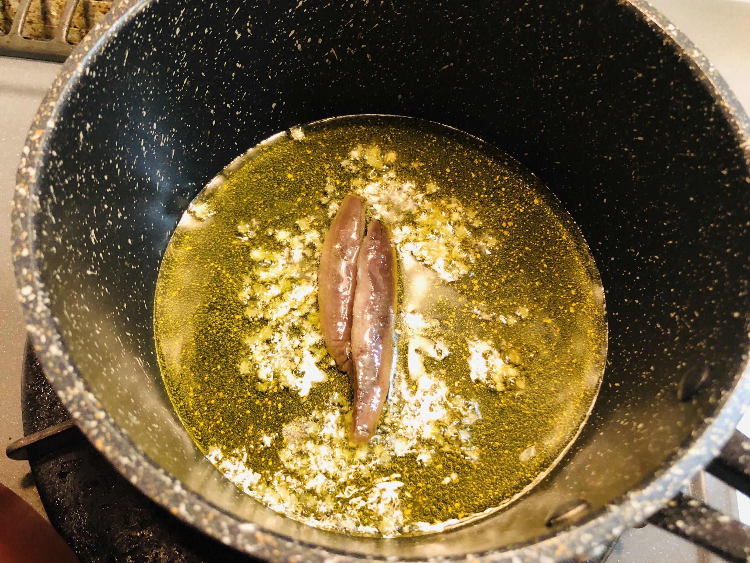 小鍋にオリーブオイルとみじん切りのにんにくを入れ、弱火で加熱し、香りが出てきたのでアンチョビを入れた状態の画像です。