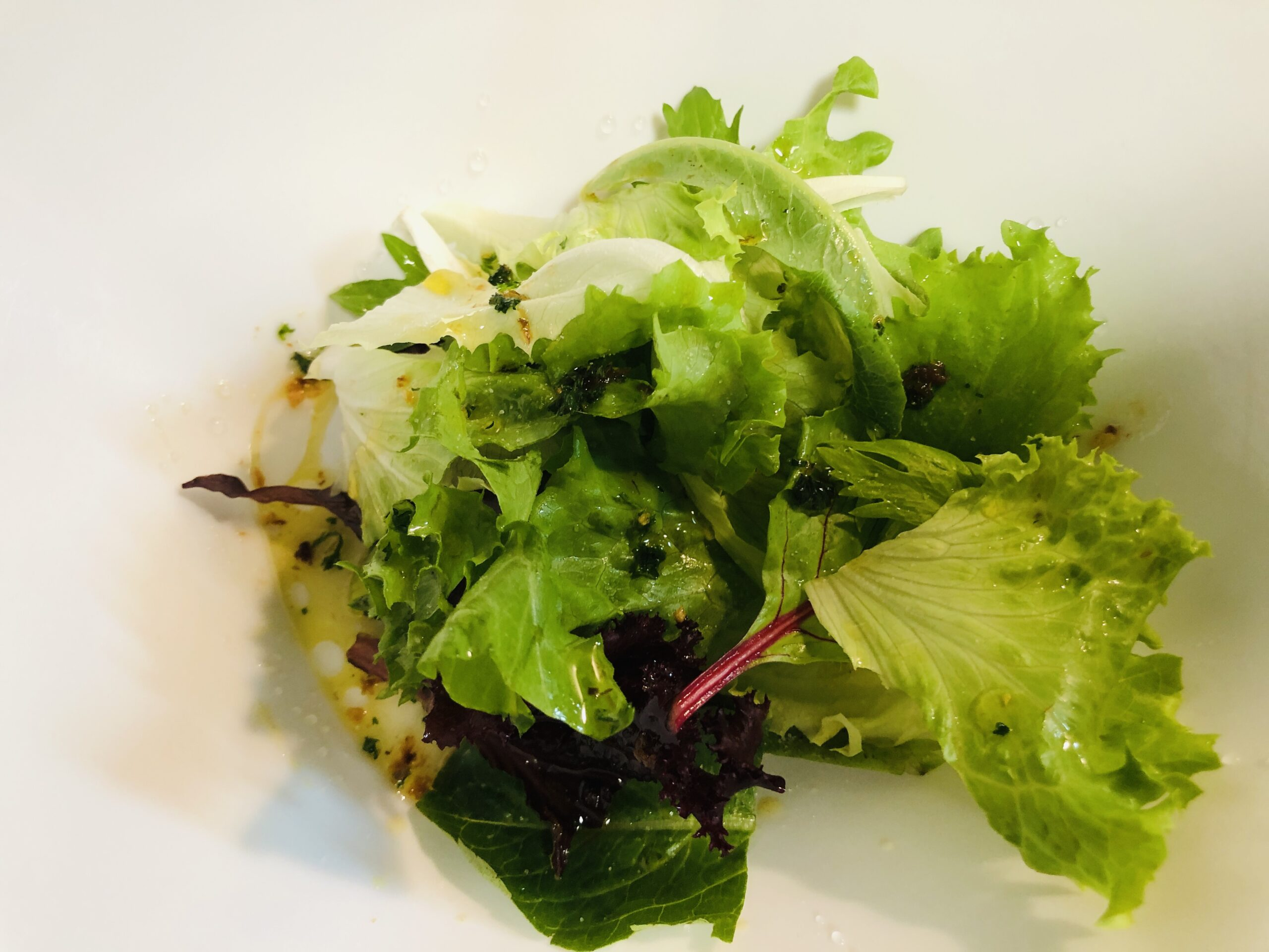 ミックスリーフサラダに塩、胡椒、レモン果汁、アンチョビオイルをかけた状態の画像です