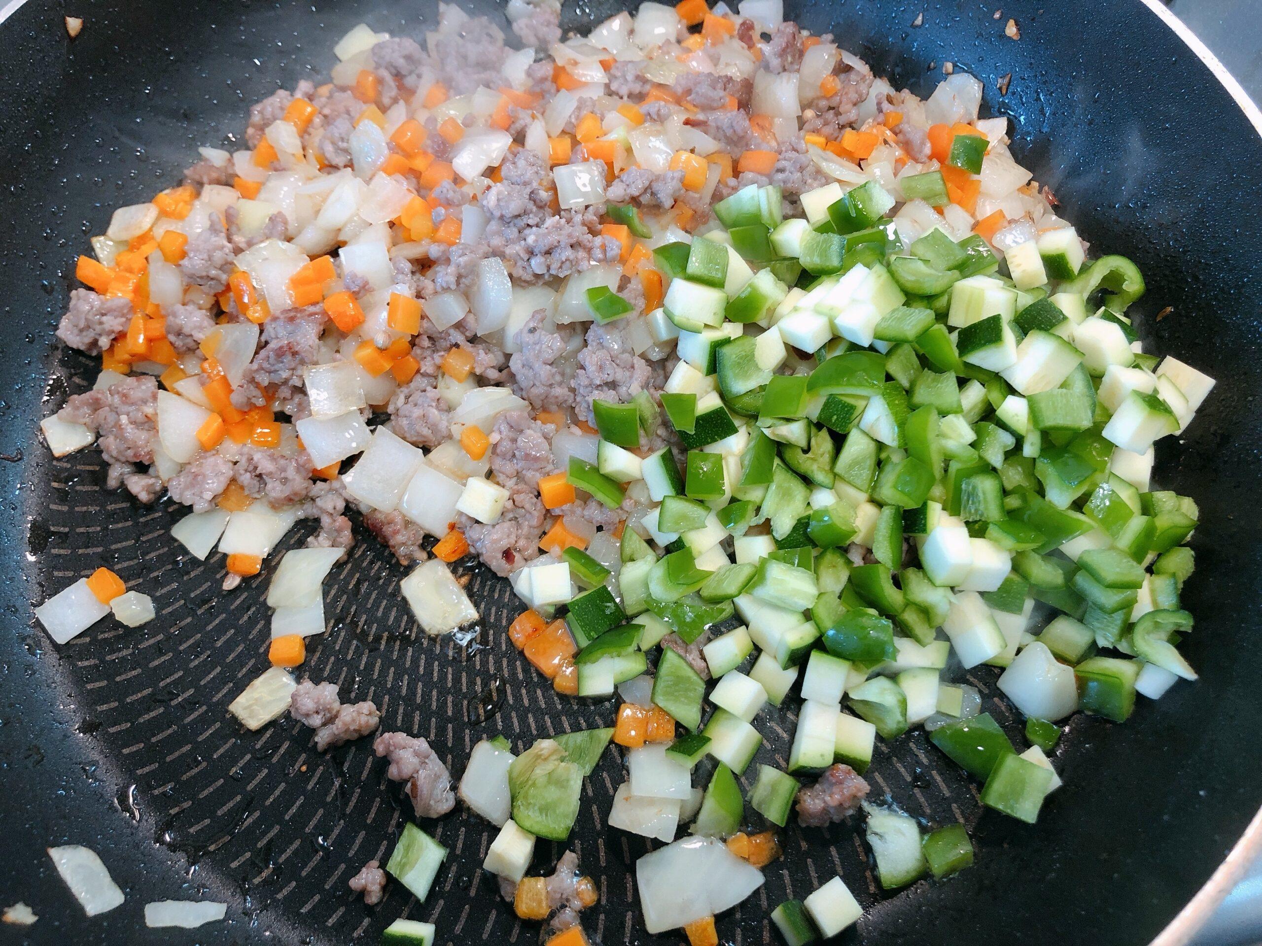香味野菜をよく炒めたので、ズッキーニとピーマンを加えた状態の画像です