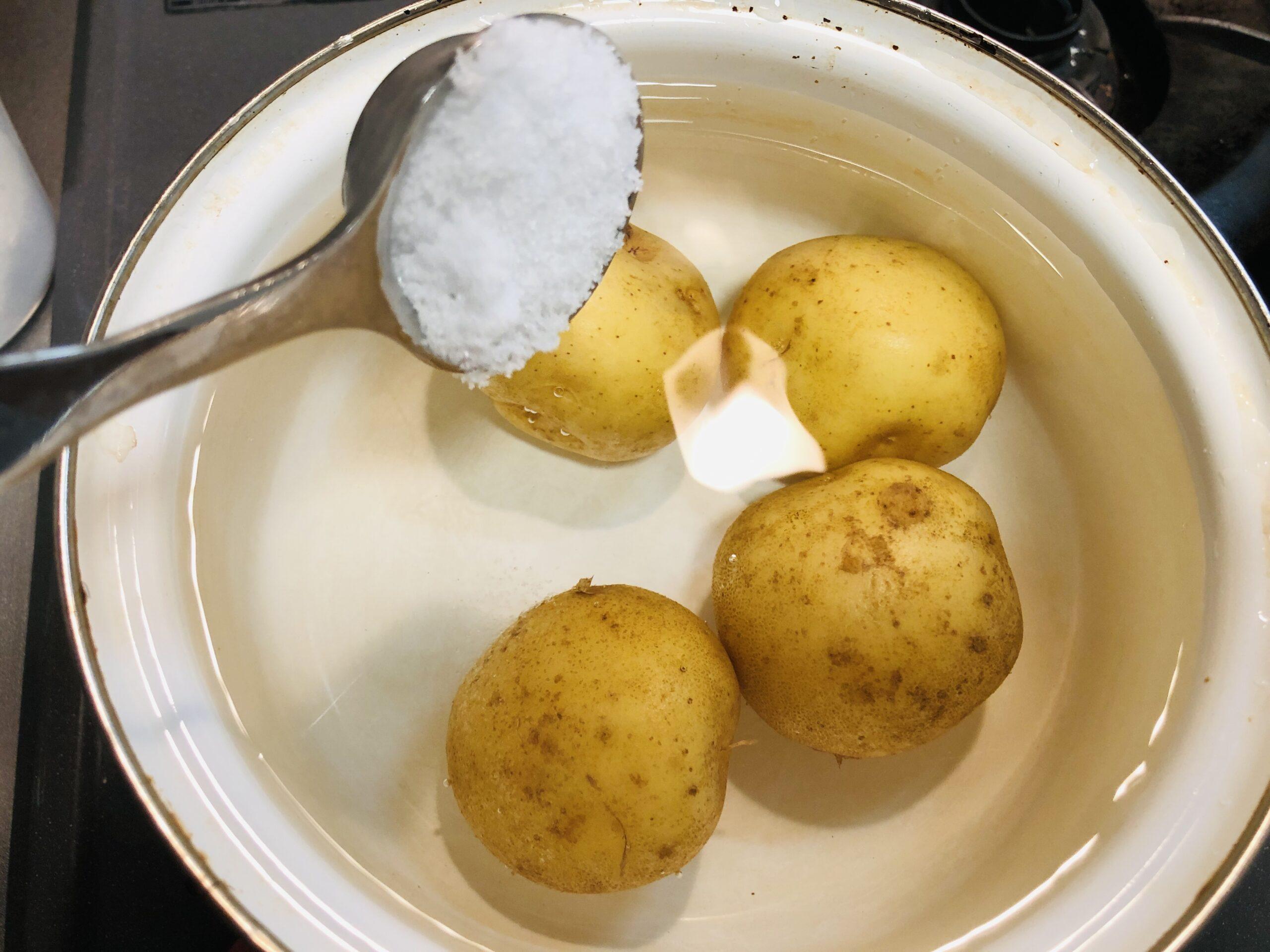 鍋にジャガイモと水をひたひたに入れ、塩を入れる様子の画像です。