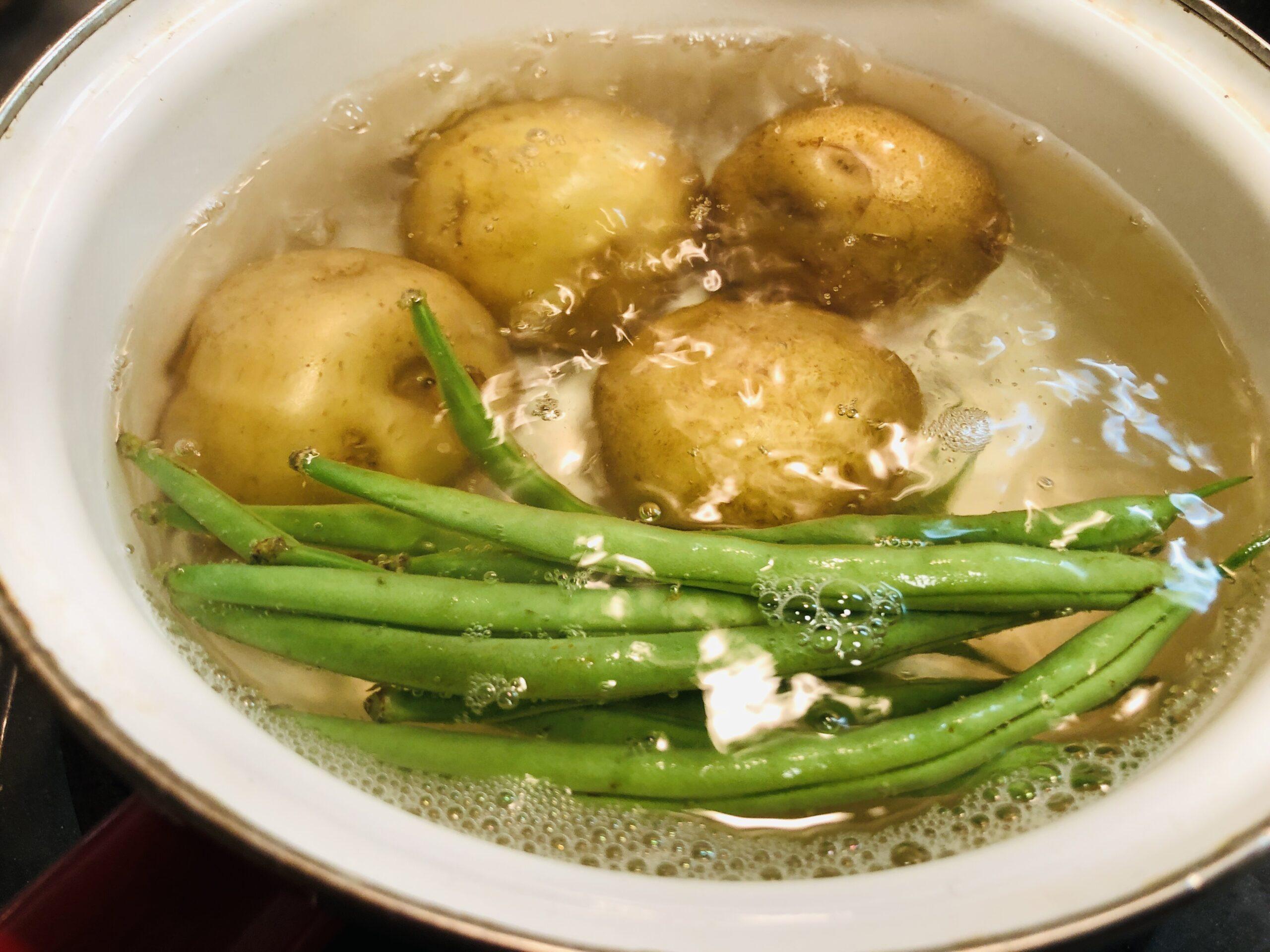 新じゃがいもが固めに茹で上がったので、インゲンを入れて、茹でている様子の画像です。