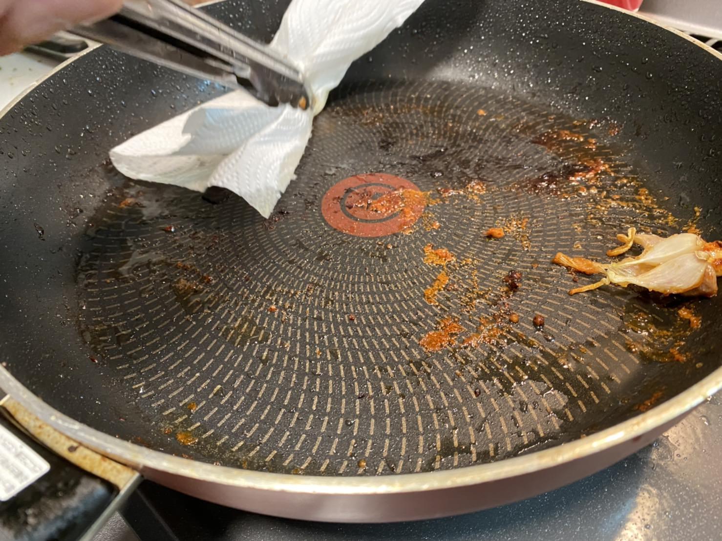 鶏もも肉を焼いたフライパンの油だけをキッチンペーパーで拭き取っている様子の画像です
