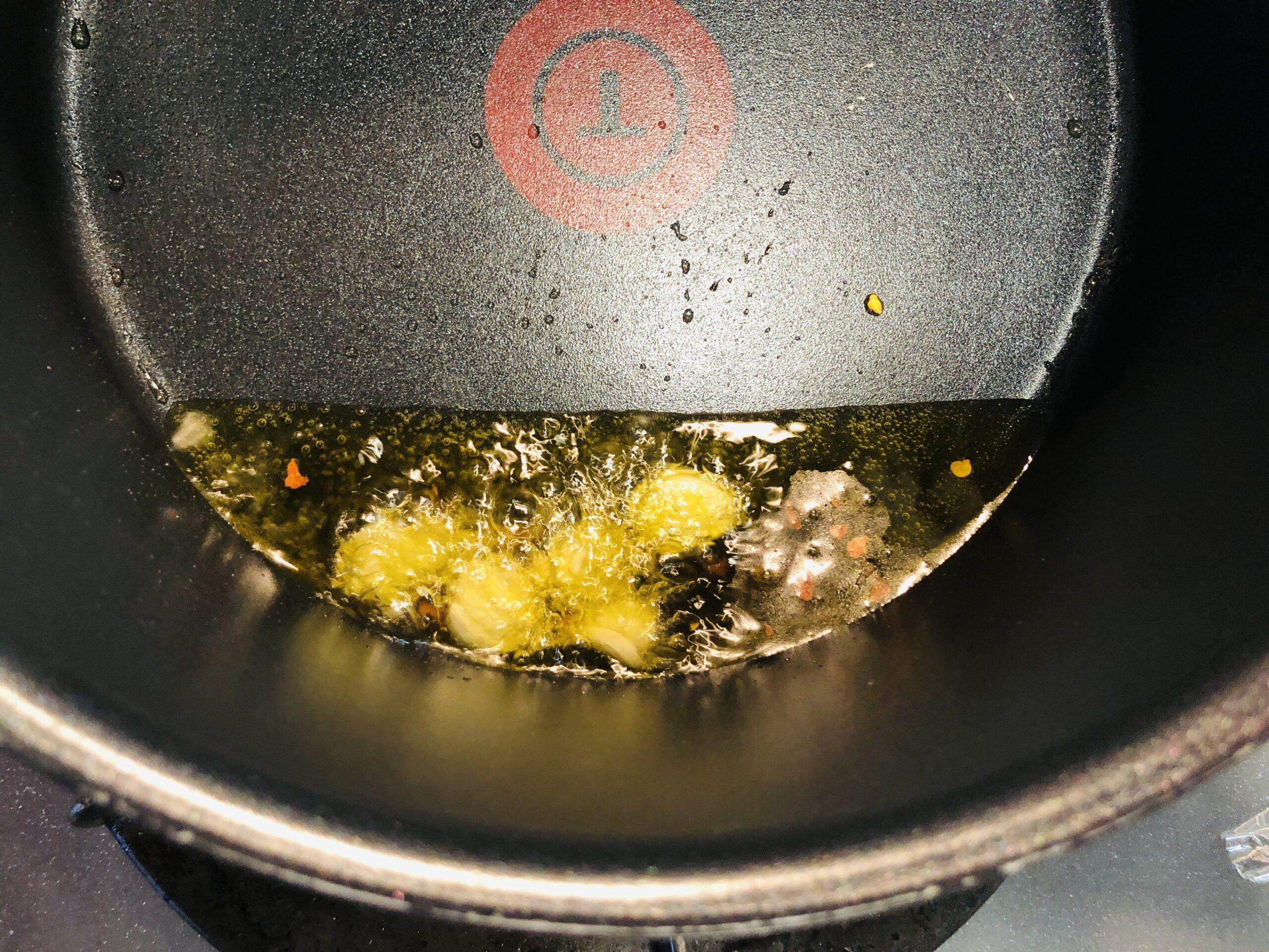 鍋にオリーブオイルと潰したニンニク、タカノツメを入れ弱火にかけている様子の画像です