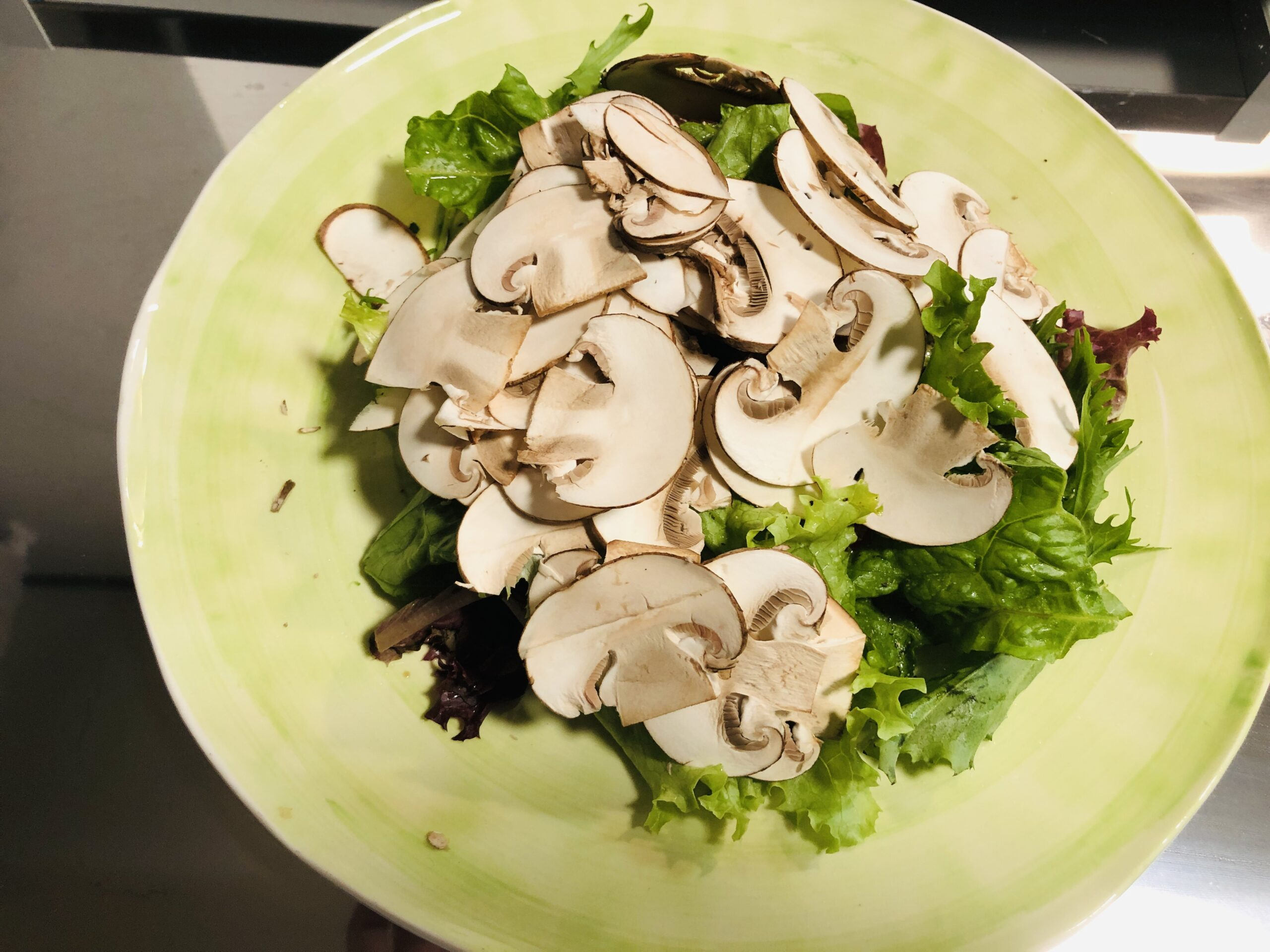 味付けしたサラダの上に生マッシュルームスライスを散らした状態の画像です