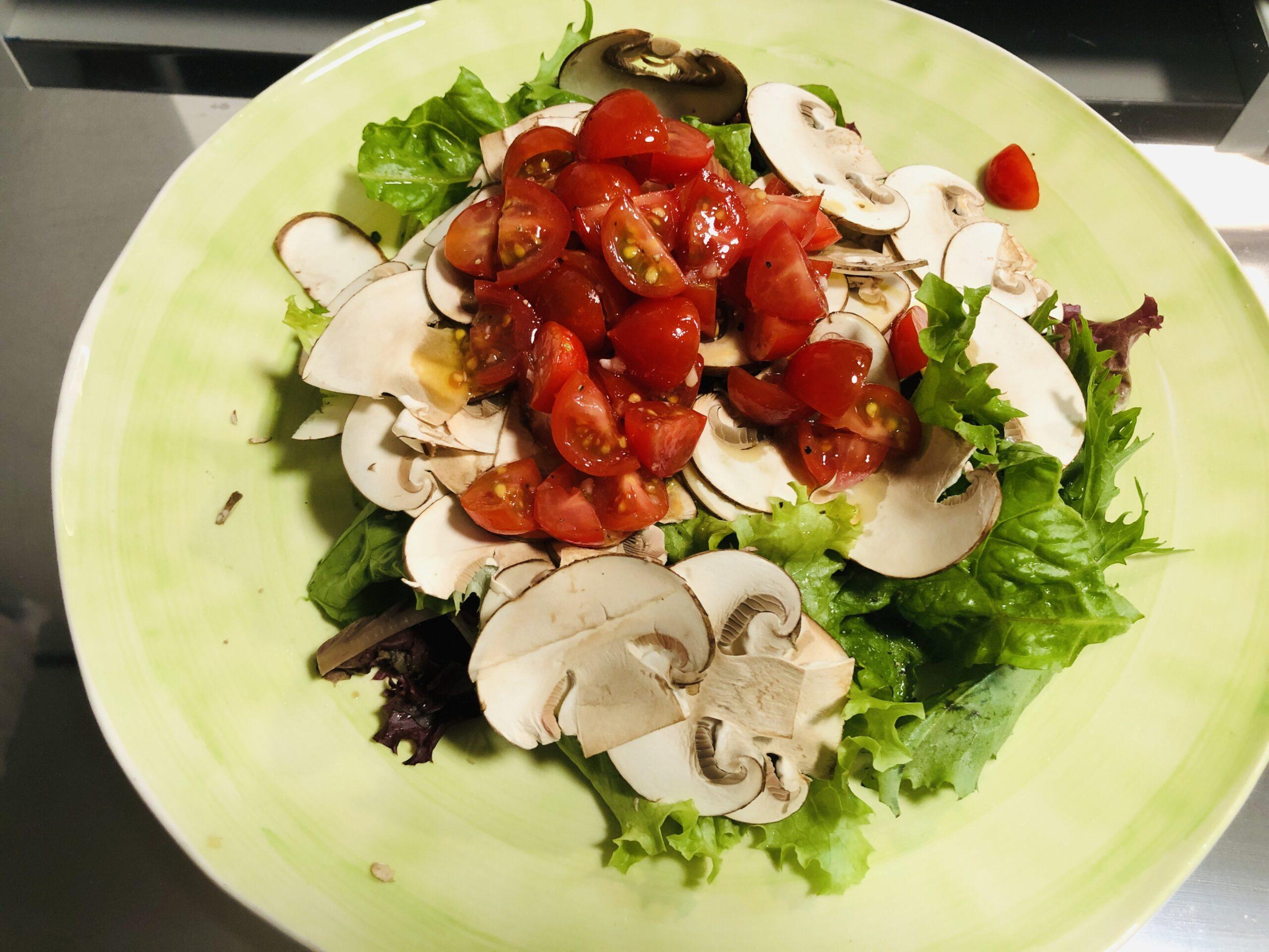 マッシュルームスライスを載せたサラダの上からミニトマトを和えたものを載せた状態の画像です