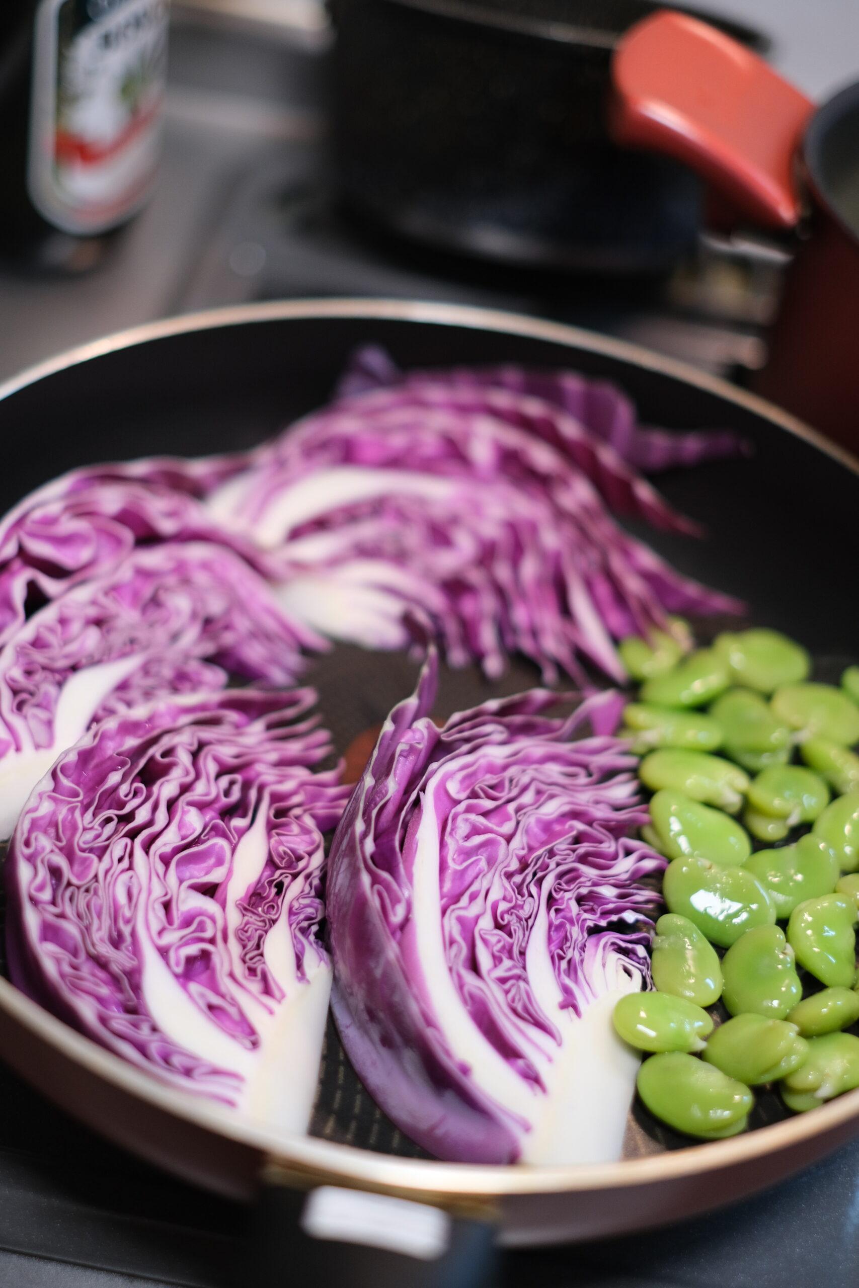 フライパンに紫キャベツとそら豆をおいた状態の画像です