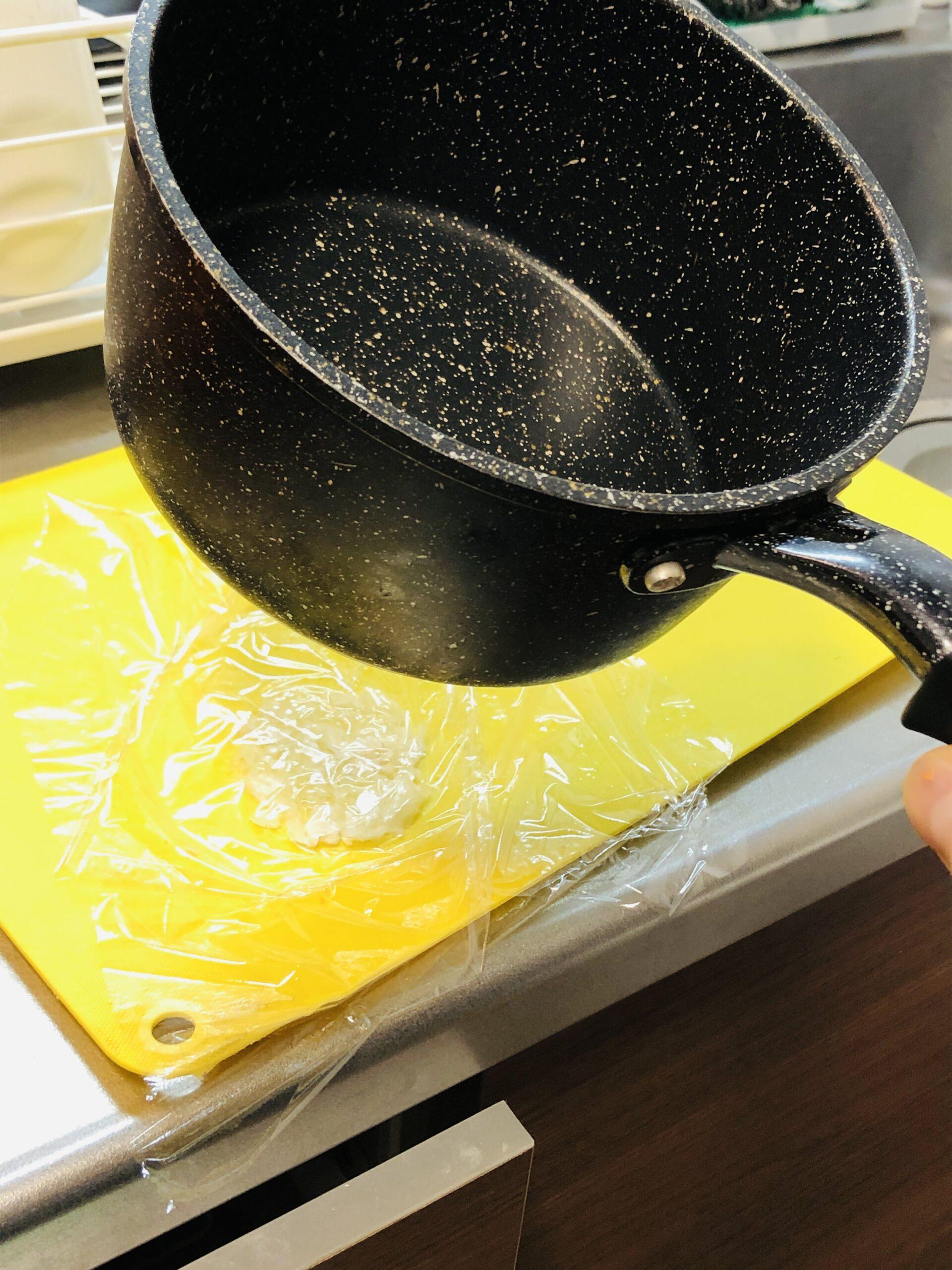 ラップをかぶせたニンニクを小鍋の底で叩き潰す様子の画像です