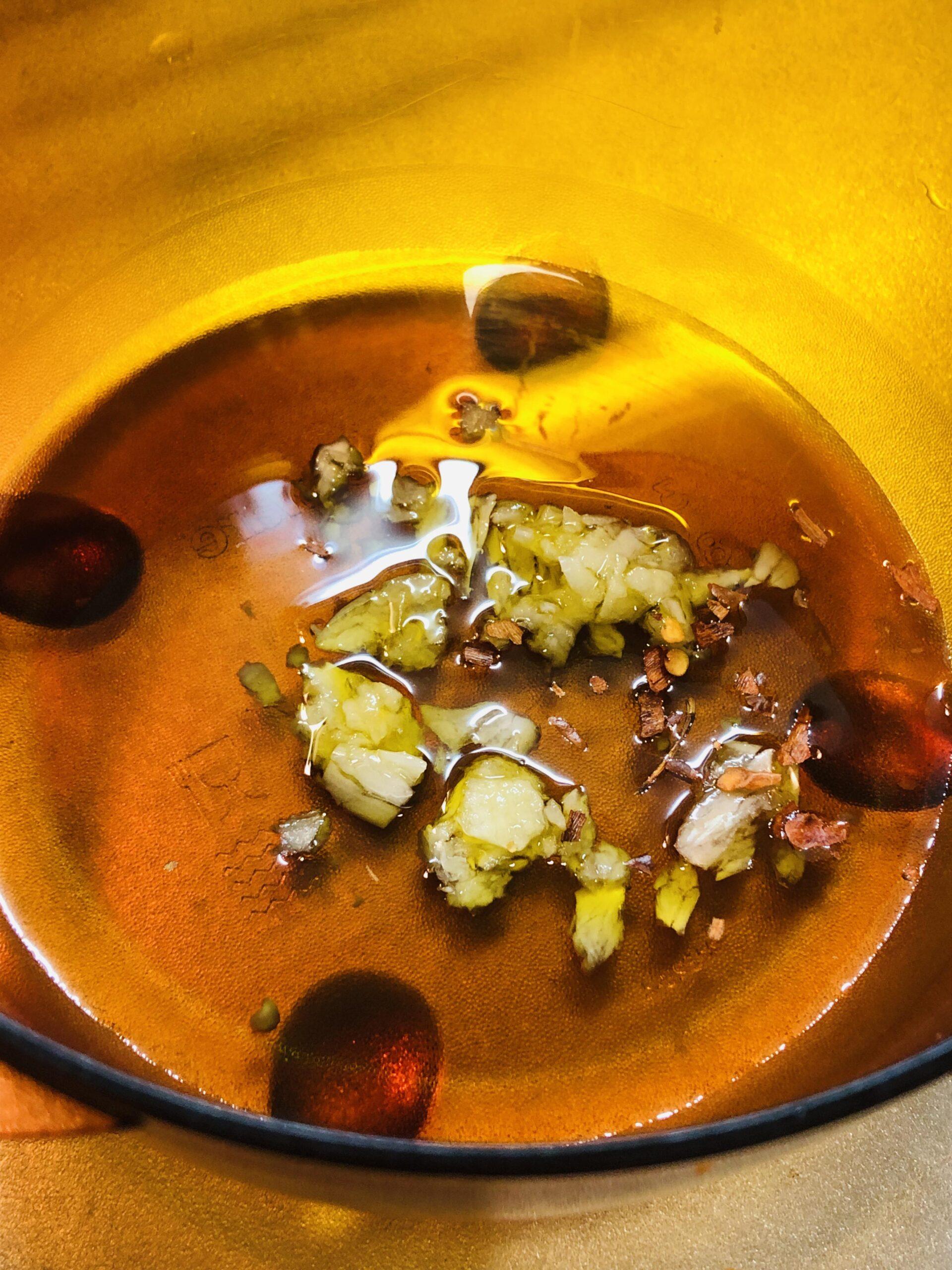 レンジ対応の容器に叩き潰したニンニクとタカノツメ、オリーブオイルを入れた様子の画像です