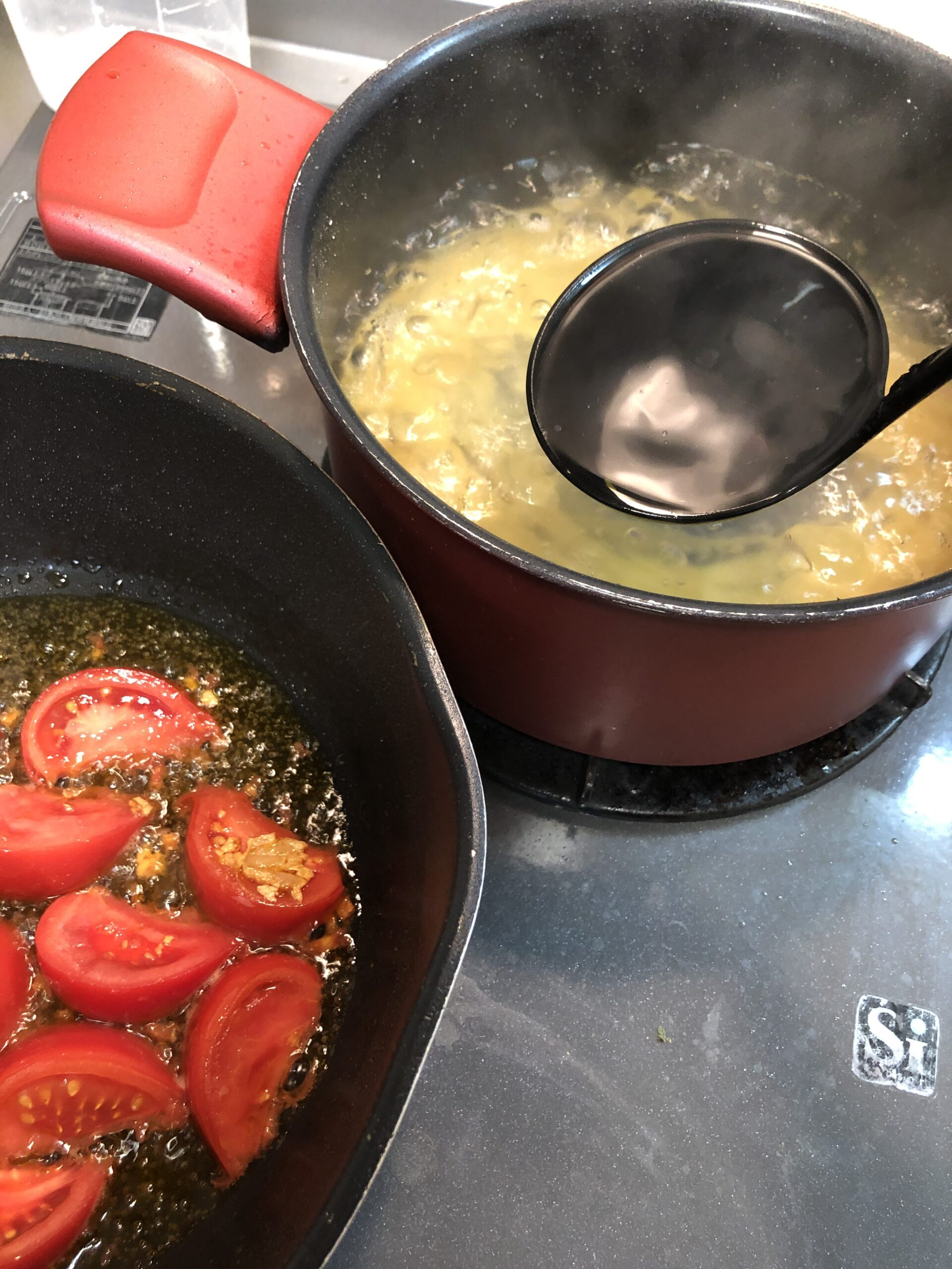 パスタの茹で汁をトマトを炒めているフライパンに入れようとしている画像です