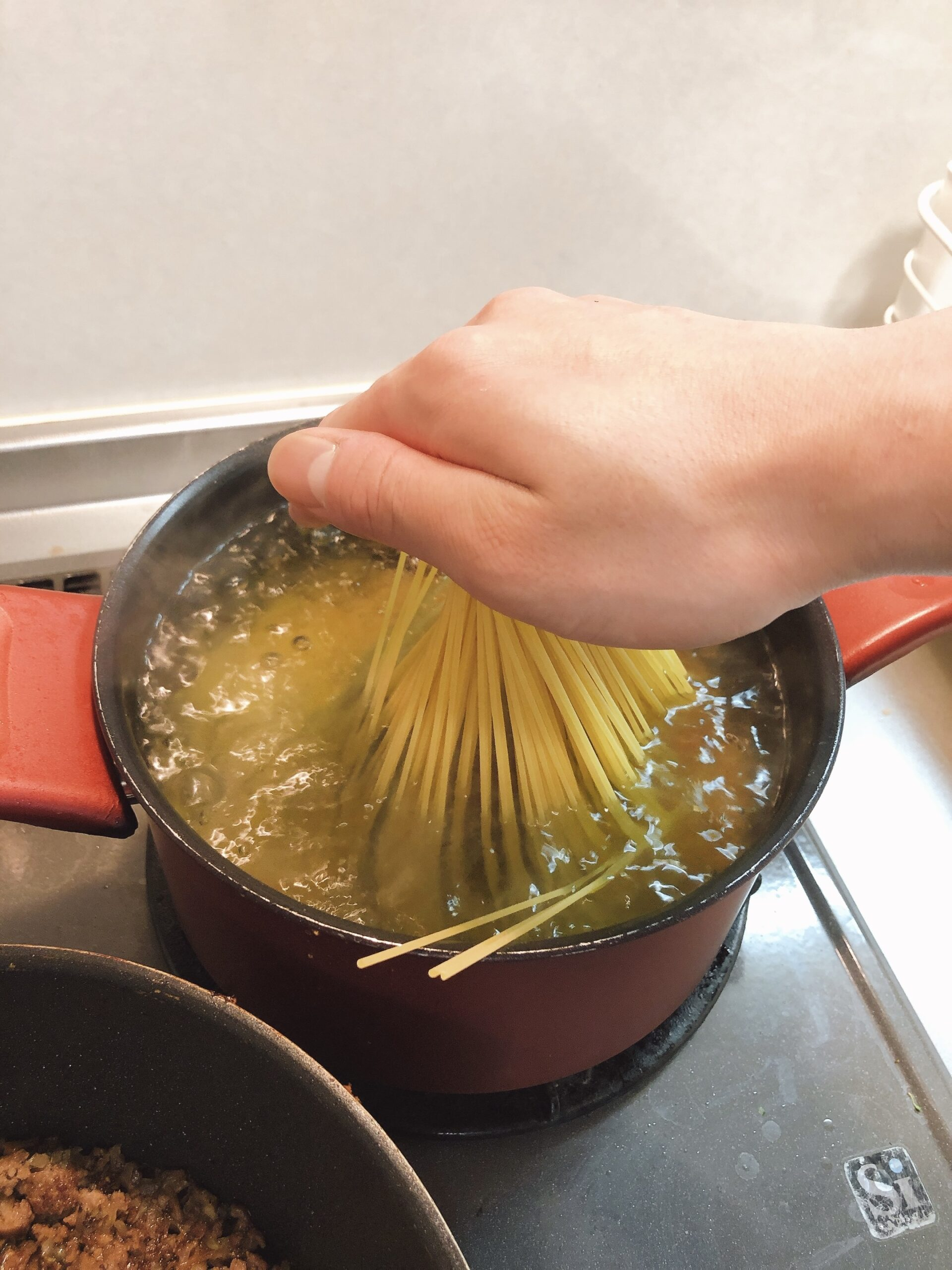 パスタを沸騰したお湯に入れている様子の画像です