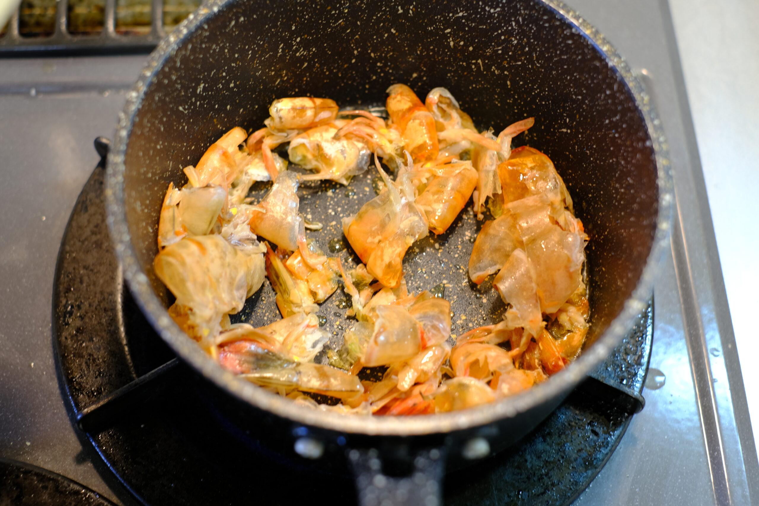 オリーブオイルで海老の殻をしっかりと炒めている様子の画像です