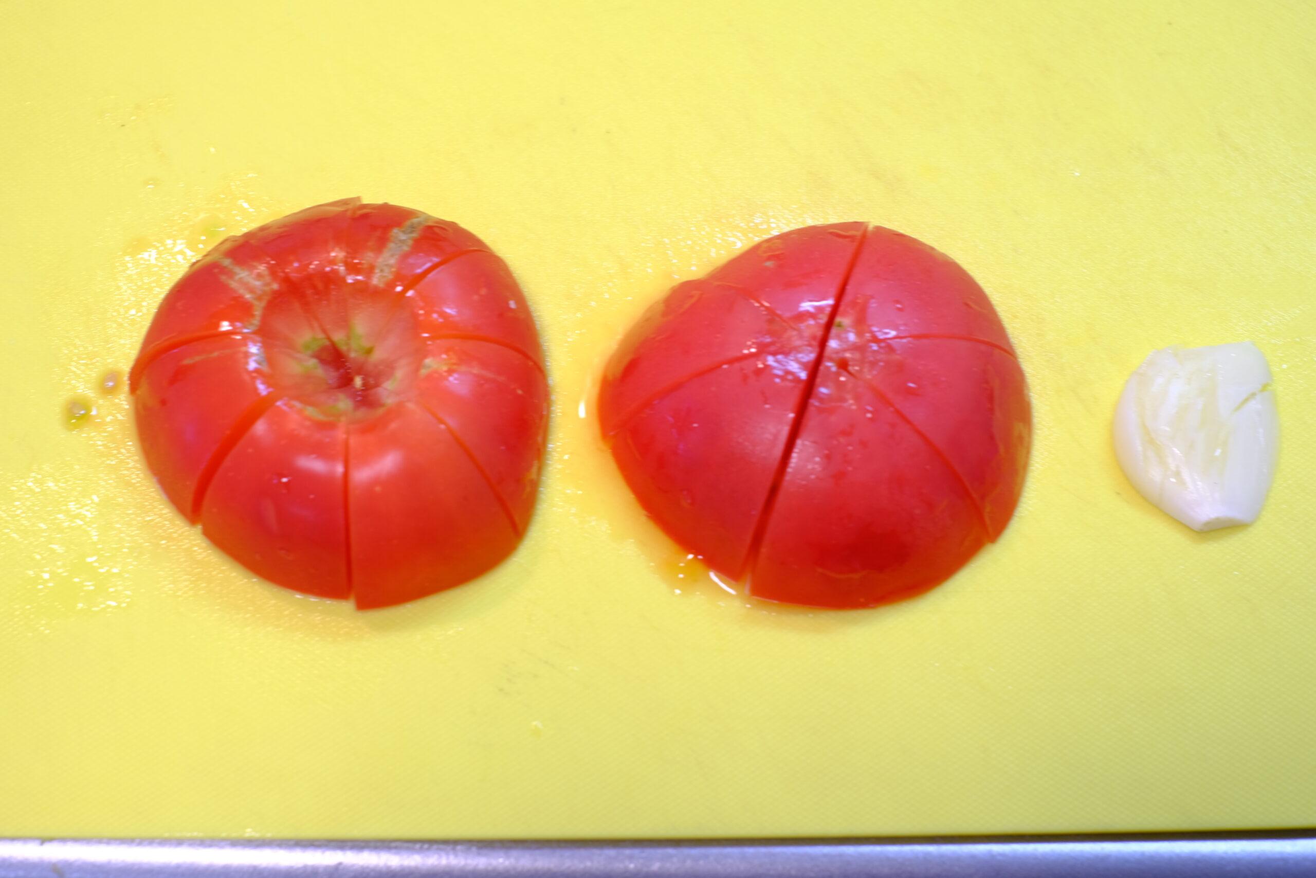 カットしたトマトと潰したニンニクの画像