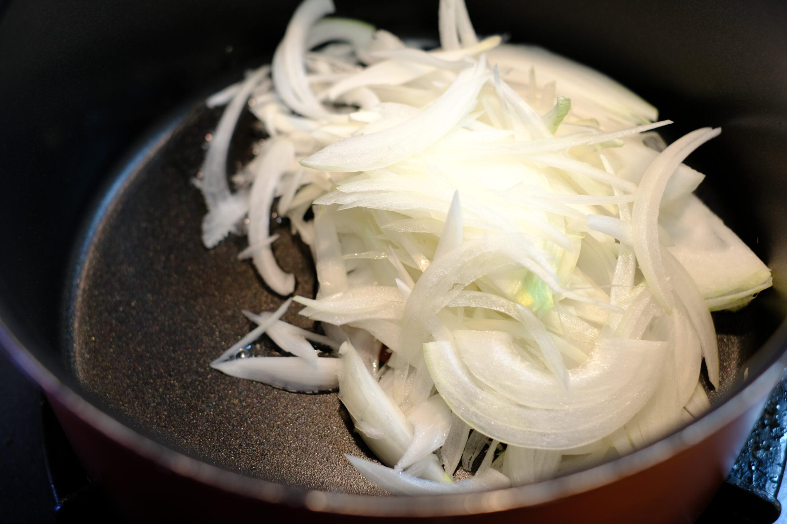 スライスした玉ねぎとサラダ油をフライパンに入れ炒め始めてた画像