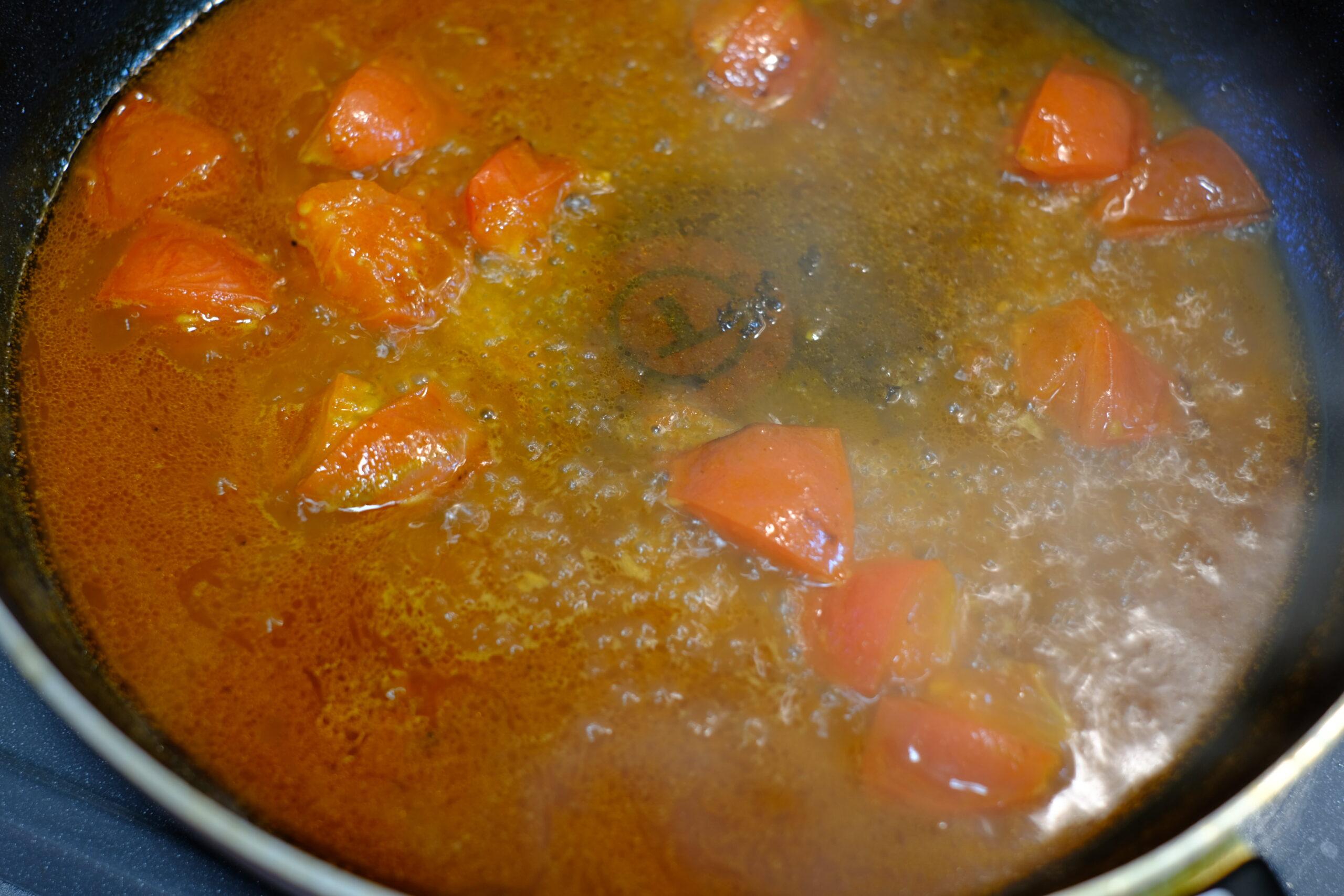 トマトを炒めたところに海老ソースを加え煮詰めている画像
