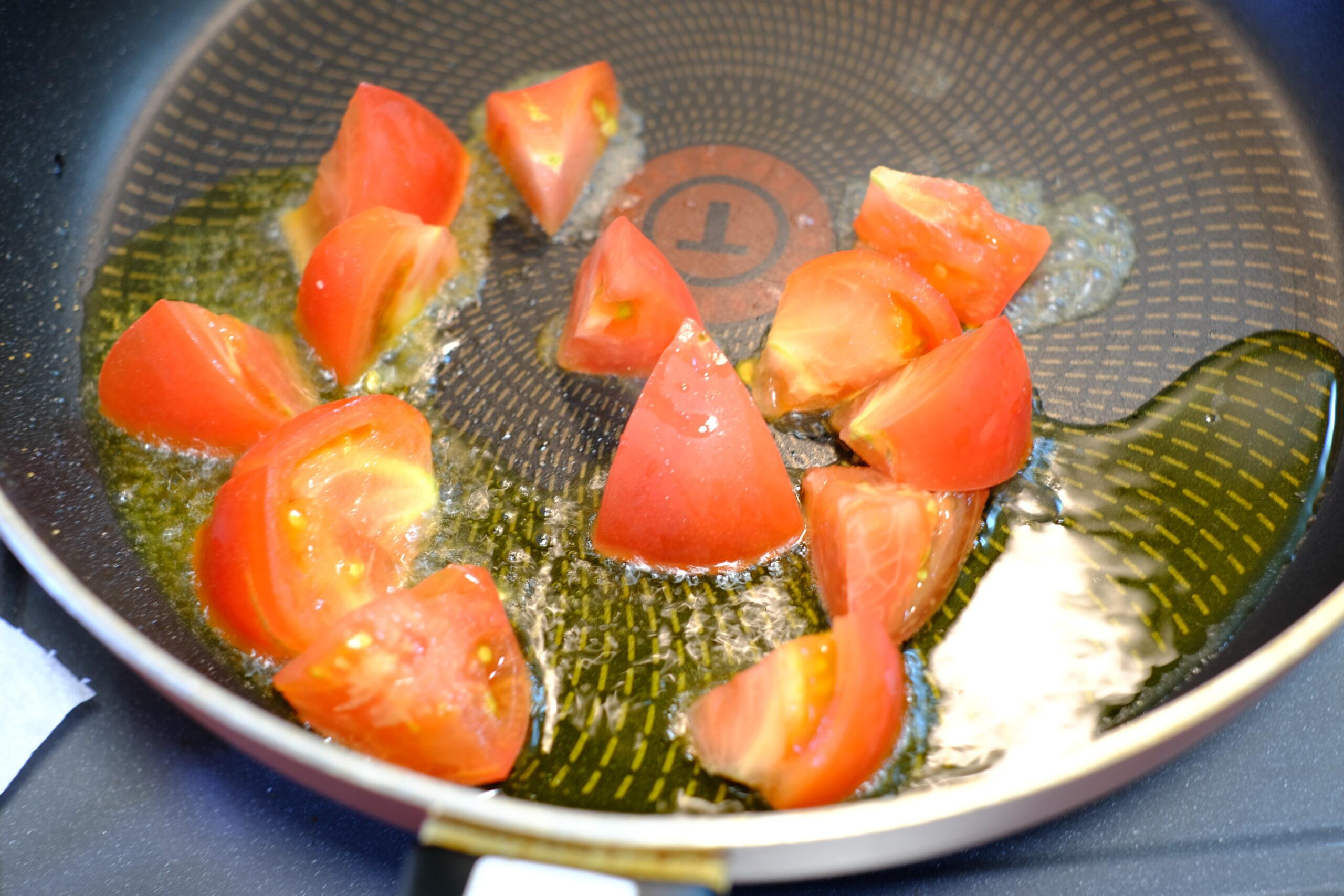 ニンニクの香りを移したオリーブオイルで、トマトを炒めている様子の画像