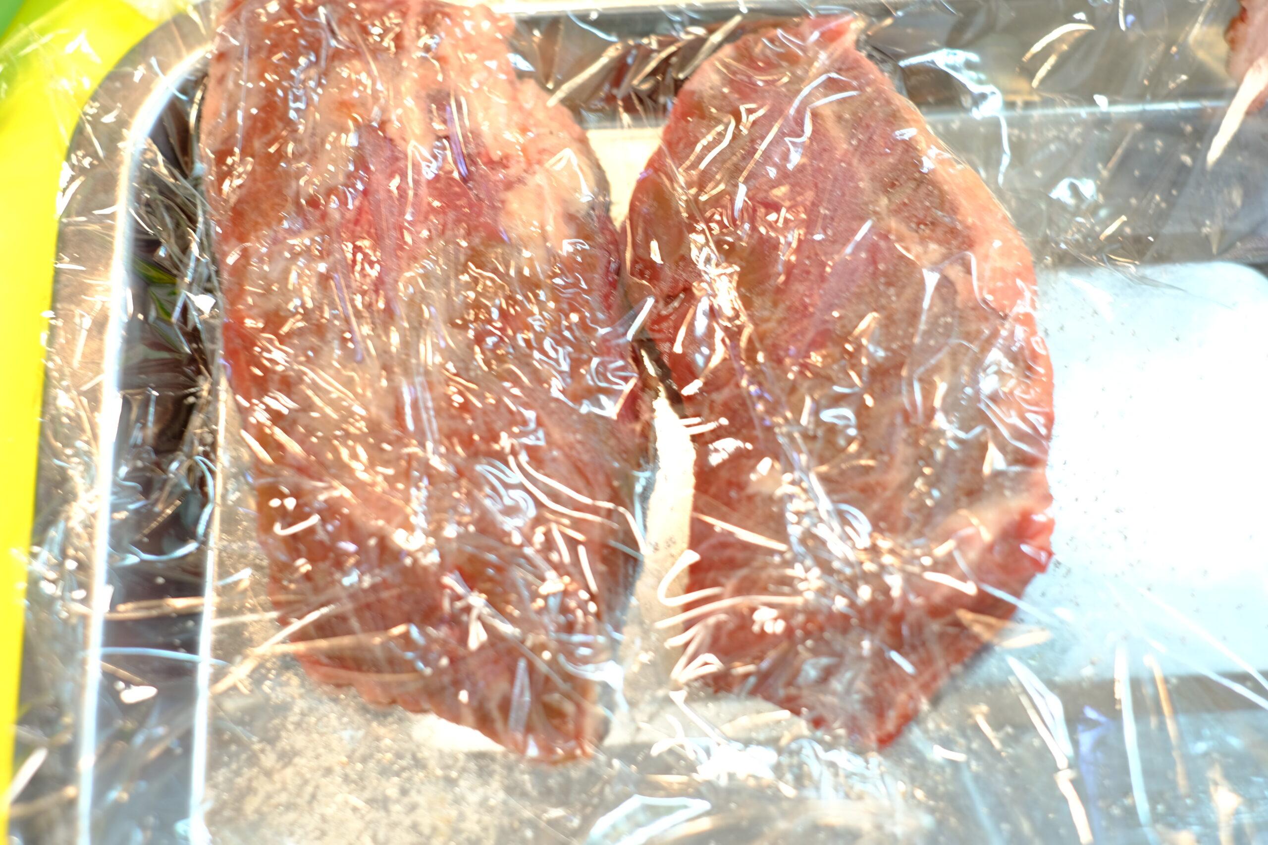 叩いて厚みを揃え、塩をふってラップをした状態の牛ハラミ肉の画像