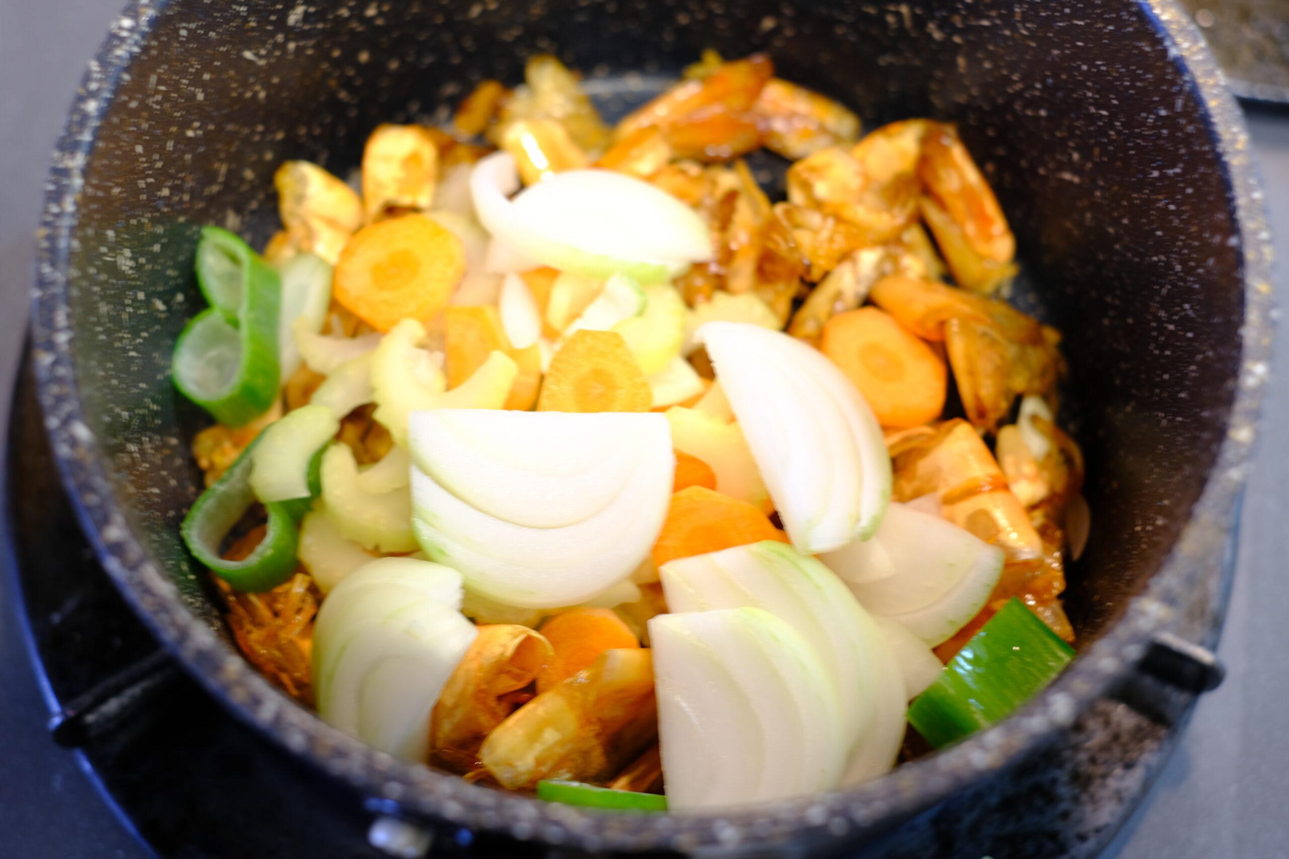 海老のソースを作る鍋に潰したニンニクとスライスした野菜を加えた画像です