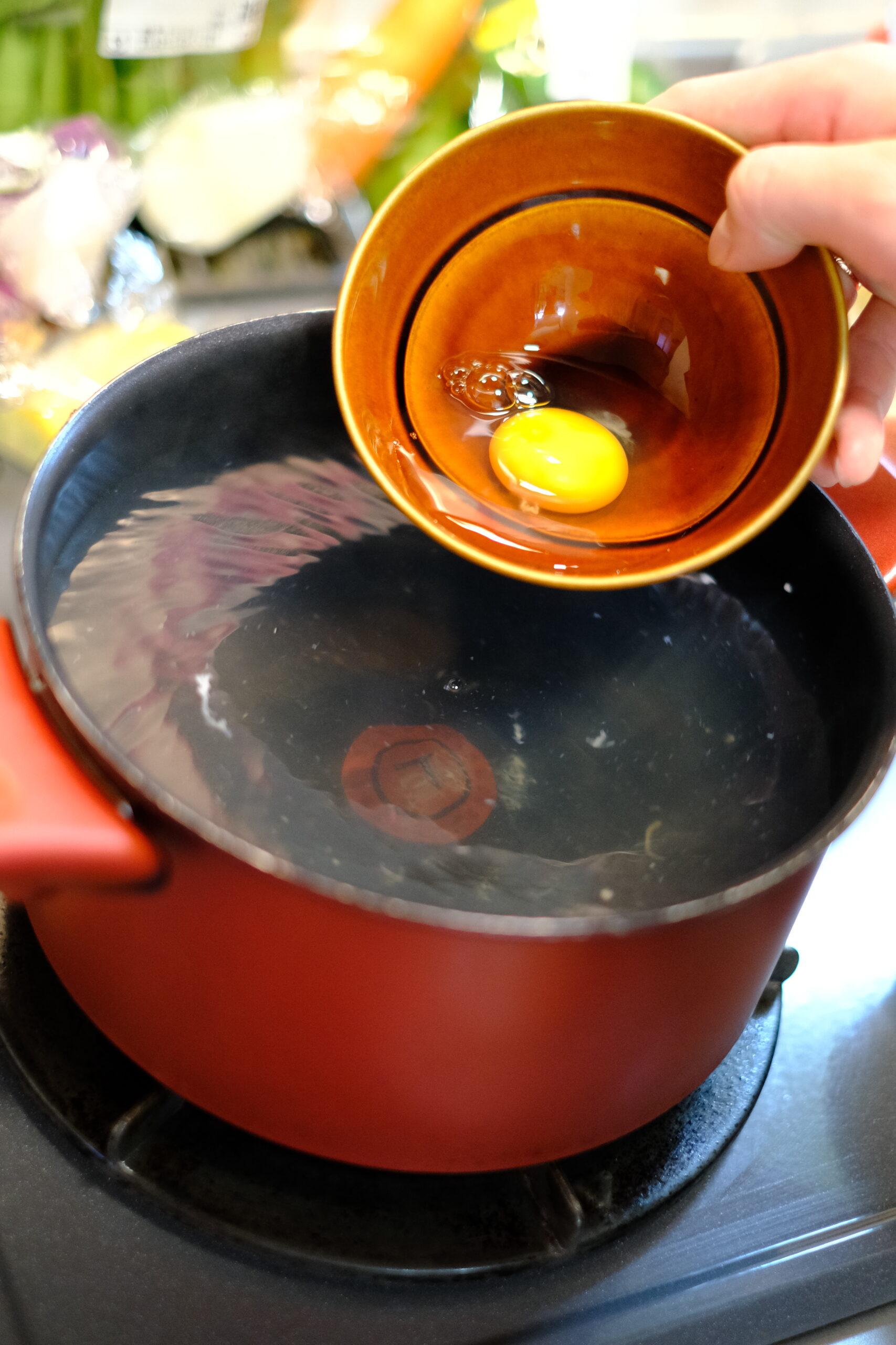 鍋のお湯の渦の中心に割った卵を入れようとしている画像です