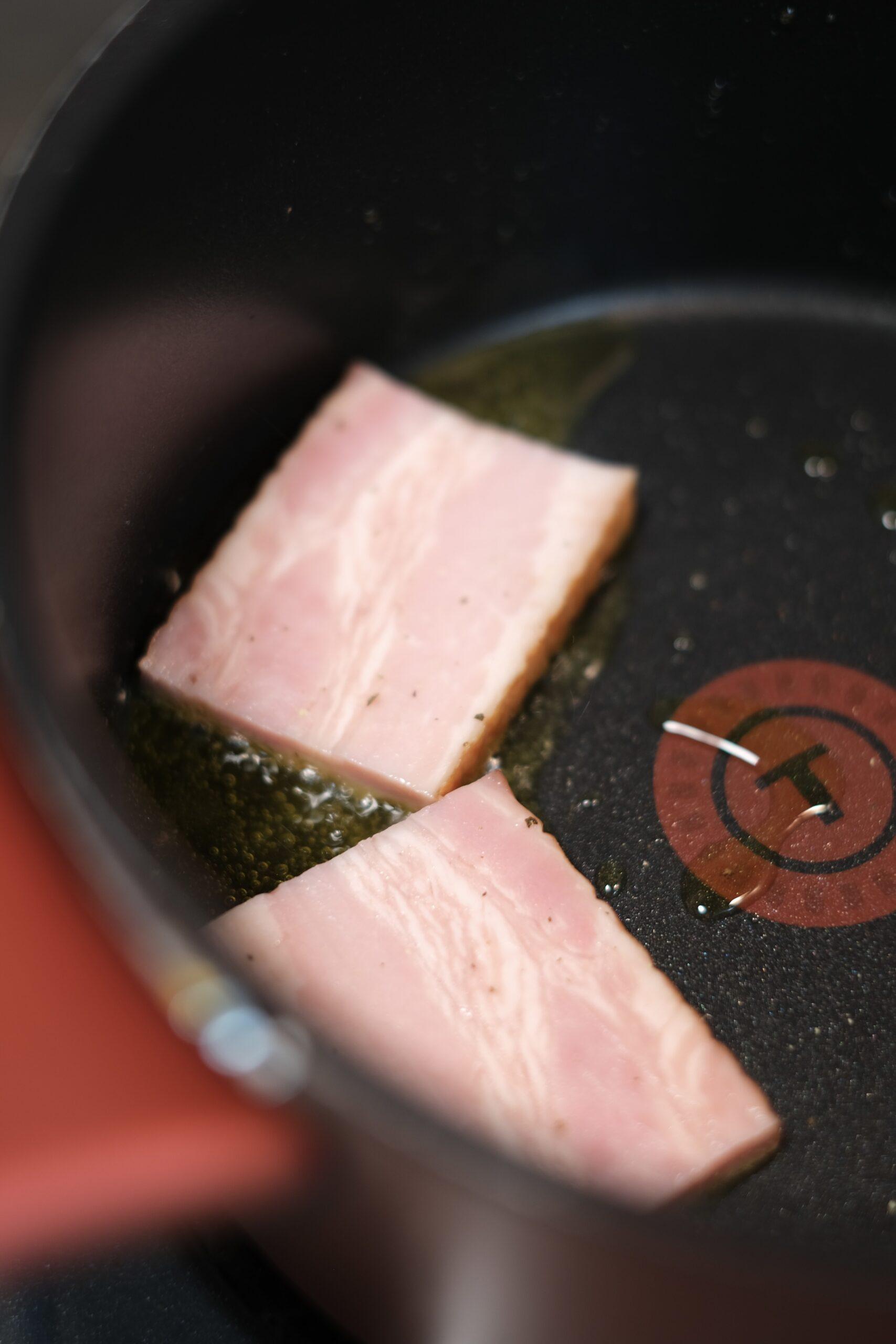フライパンでベーコンを焼いている様子の画像です