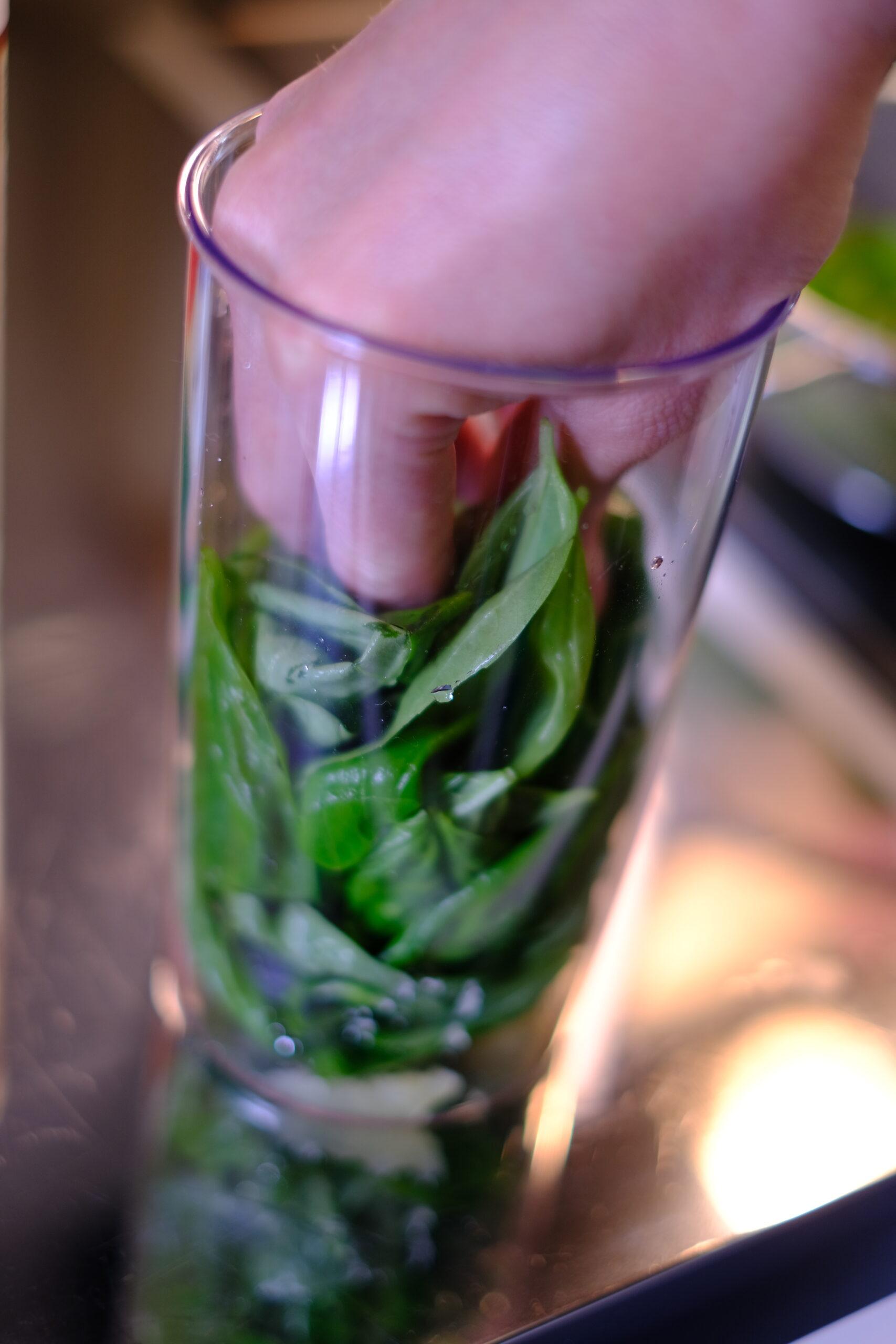 バジルの葉をハンドブレンダー専用容器に手で押し込んでいる様子の画像です
