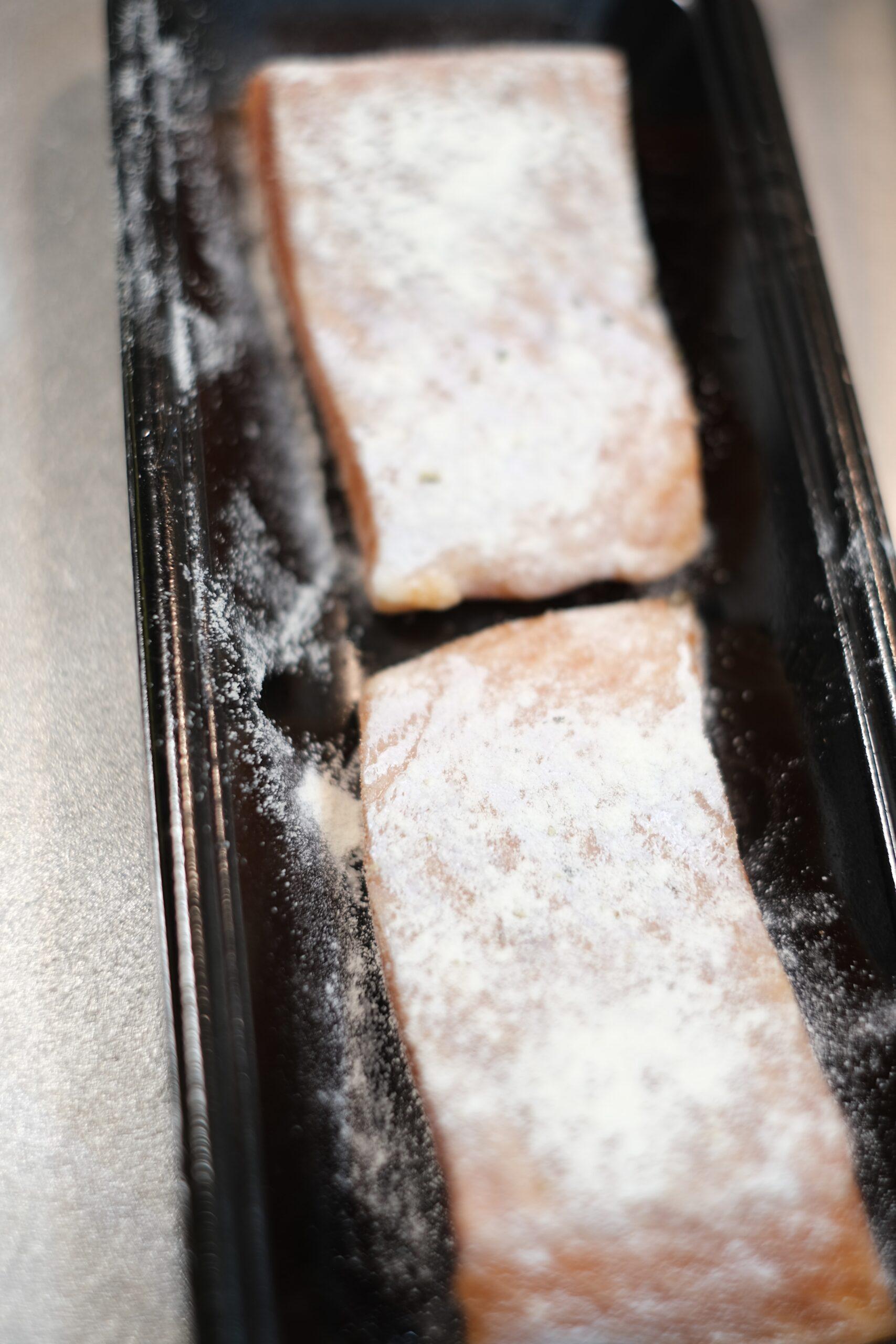 塩、こしょうして薄力粉を付けたサーモンの切り身画像です