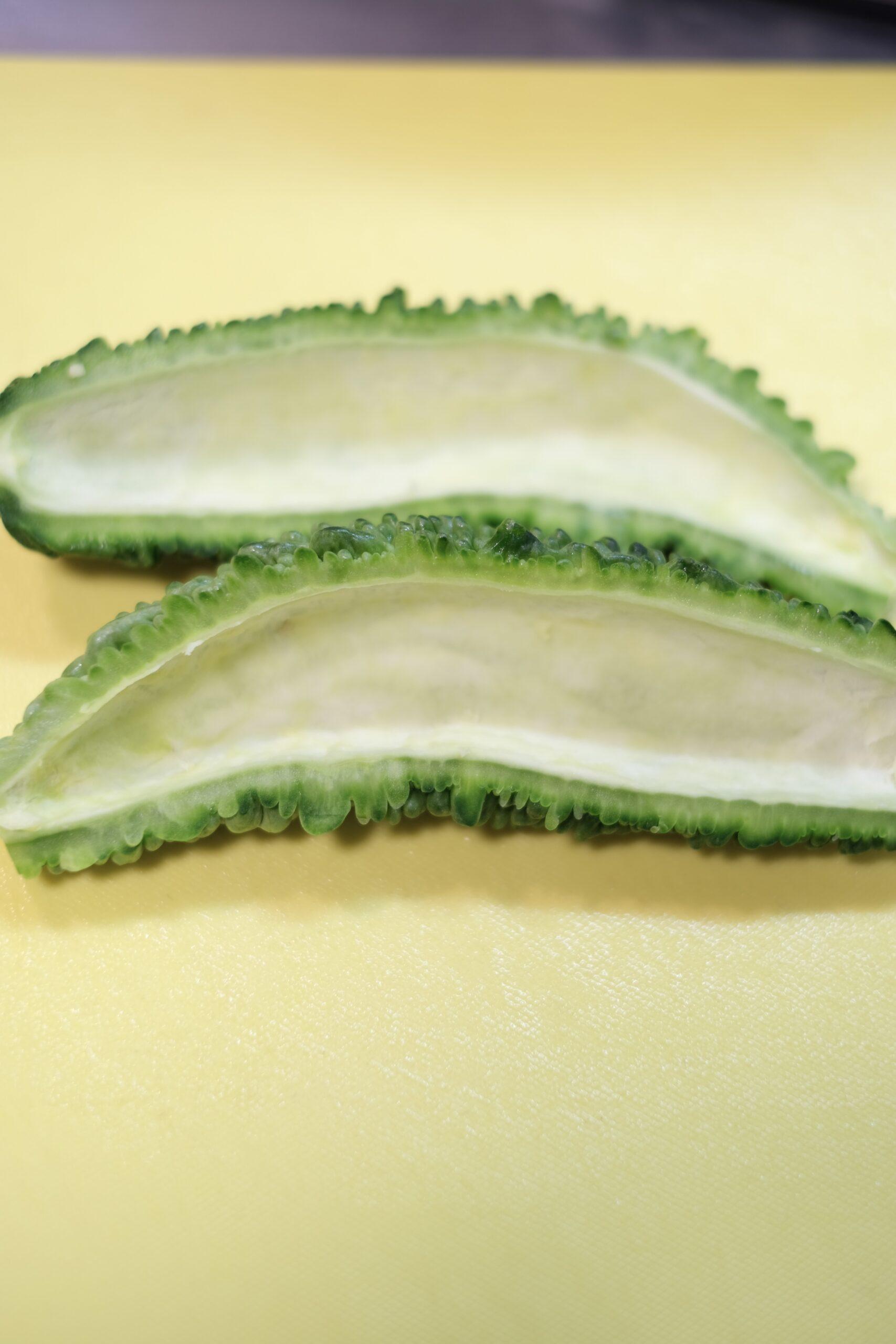 ゴーヤの両端を切り落として、縦に半分に割り、種と綿を取り除いた状態の画像です