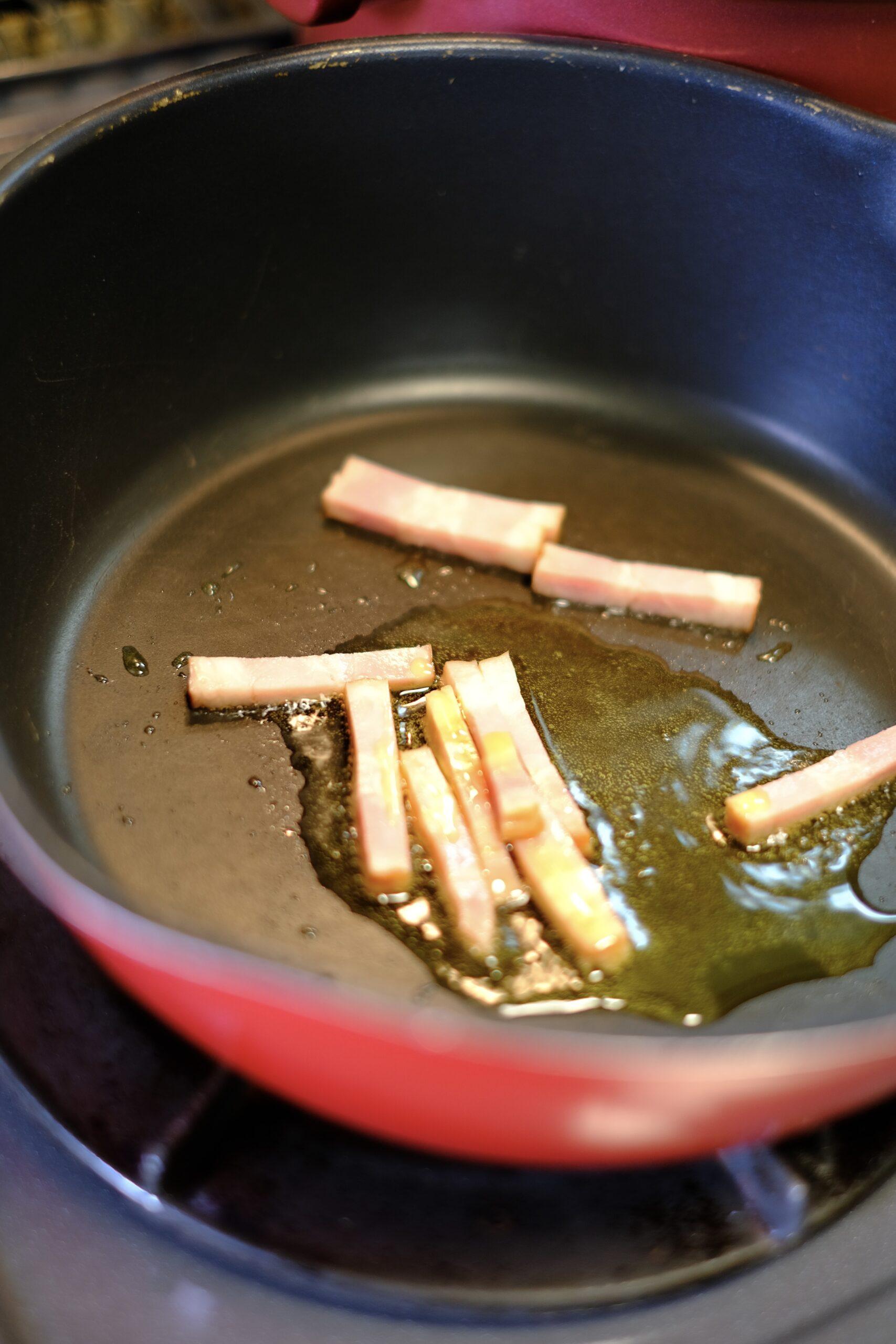 フライパンにオリーブオイルとベーコンを入れ加熱している様子の画像です