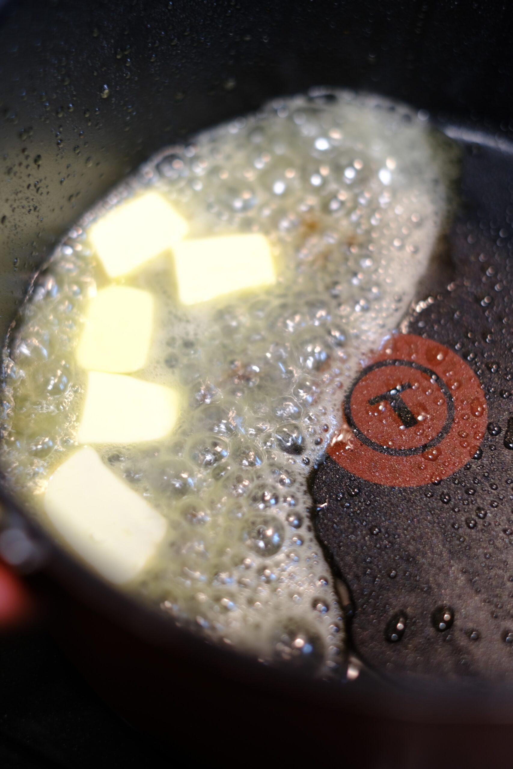 ベーコンを焼いたフライパンにバターを入れ加熱している様子の画像です