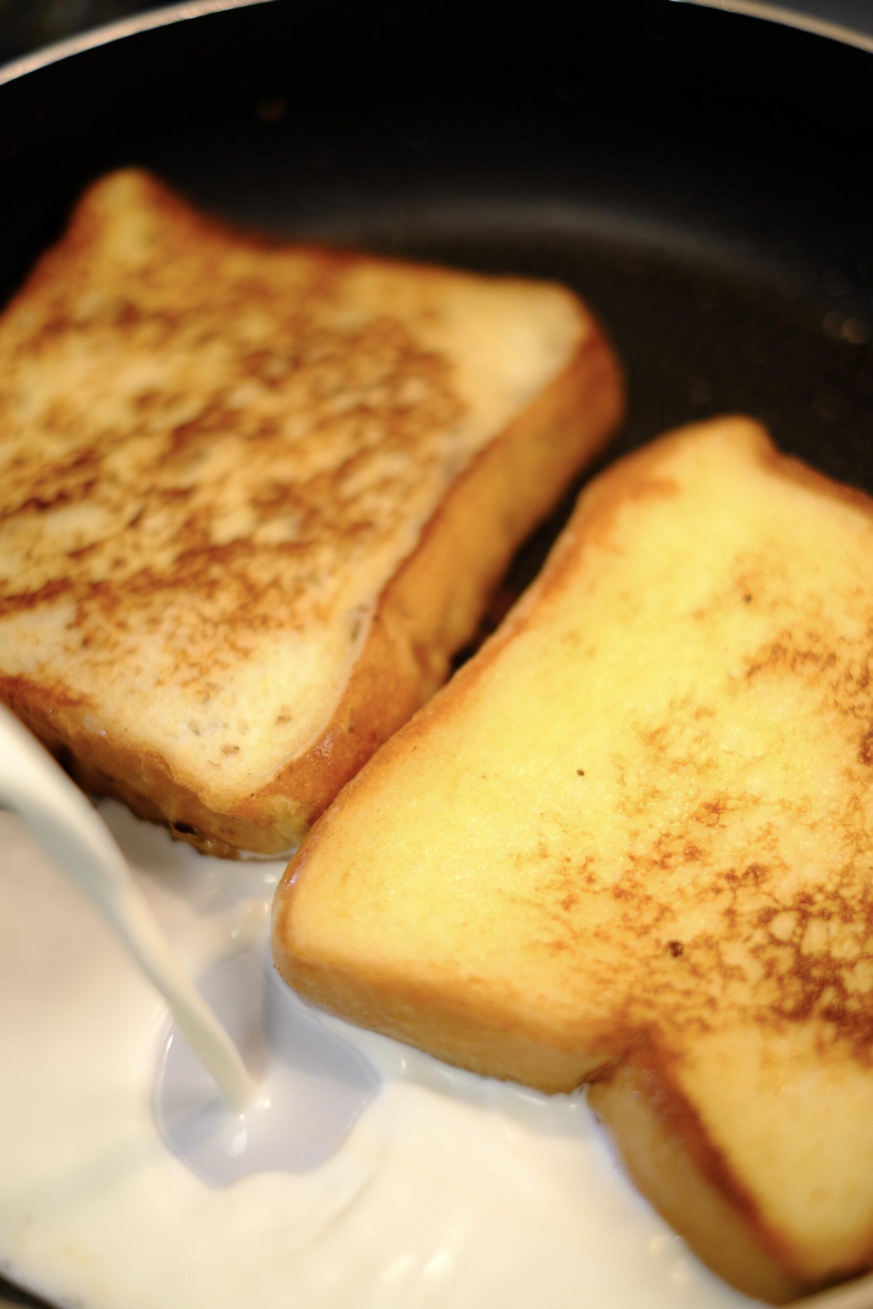 パンを焼いているフライパンに牛乳と生クリームを加えているようすの画像です