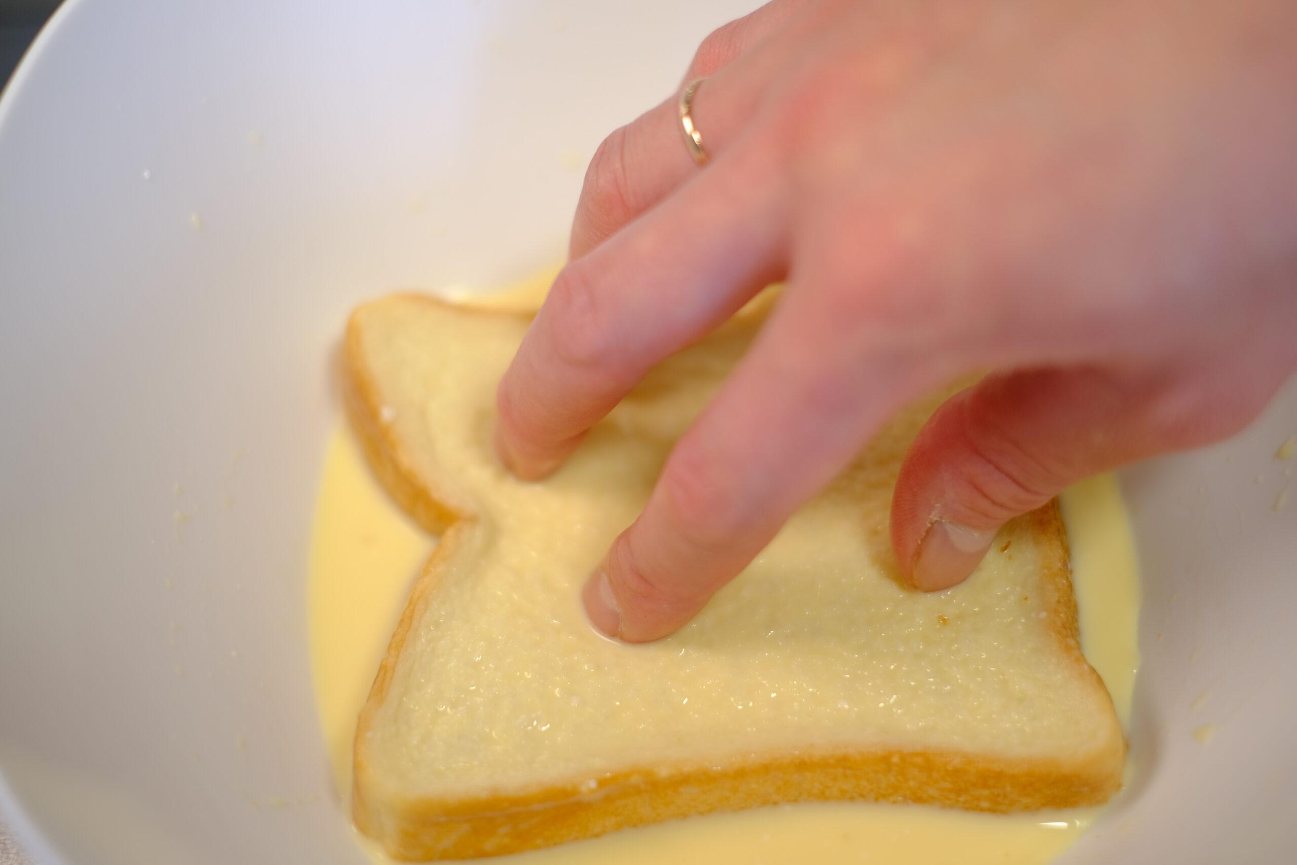 ボウルに作った漬け液に食パンを漬け込んでいるようすの画像です