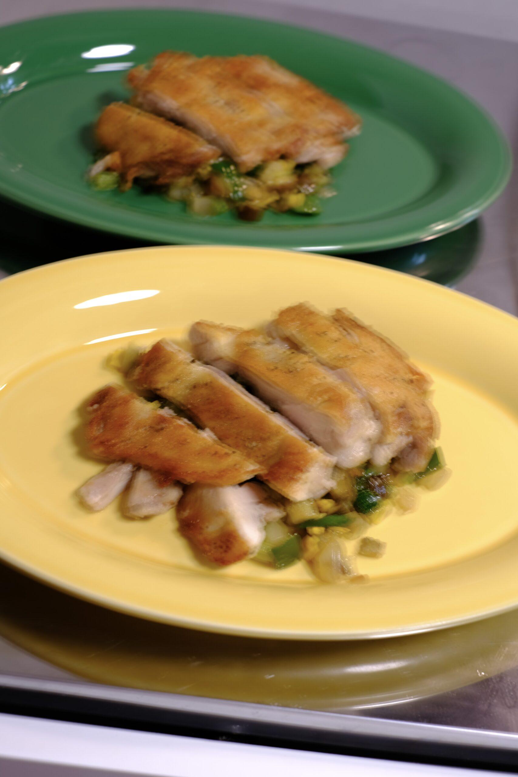 夏野菜のソテーの上にカットした鶏もも肉を盛り付けた様子の画像です