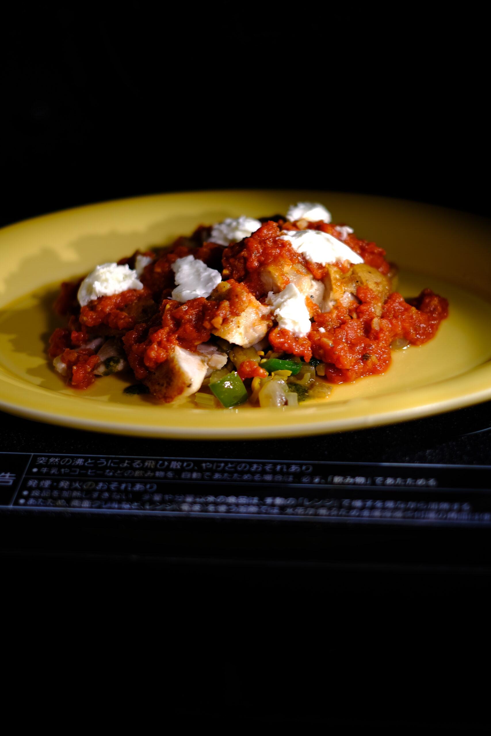 アンチョビトマトソースをまわしかけ、手でちぎったモッツァレラチーズをのせ、レンジで加熱している様子の画像です
