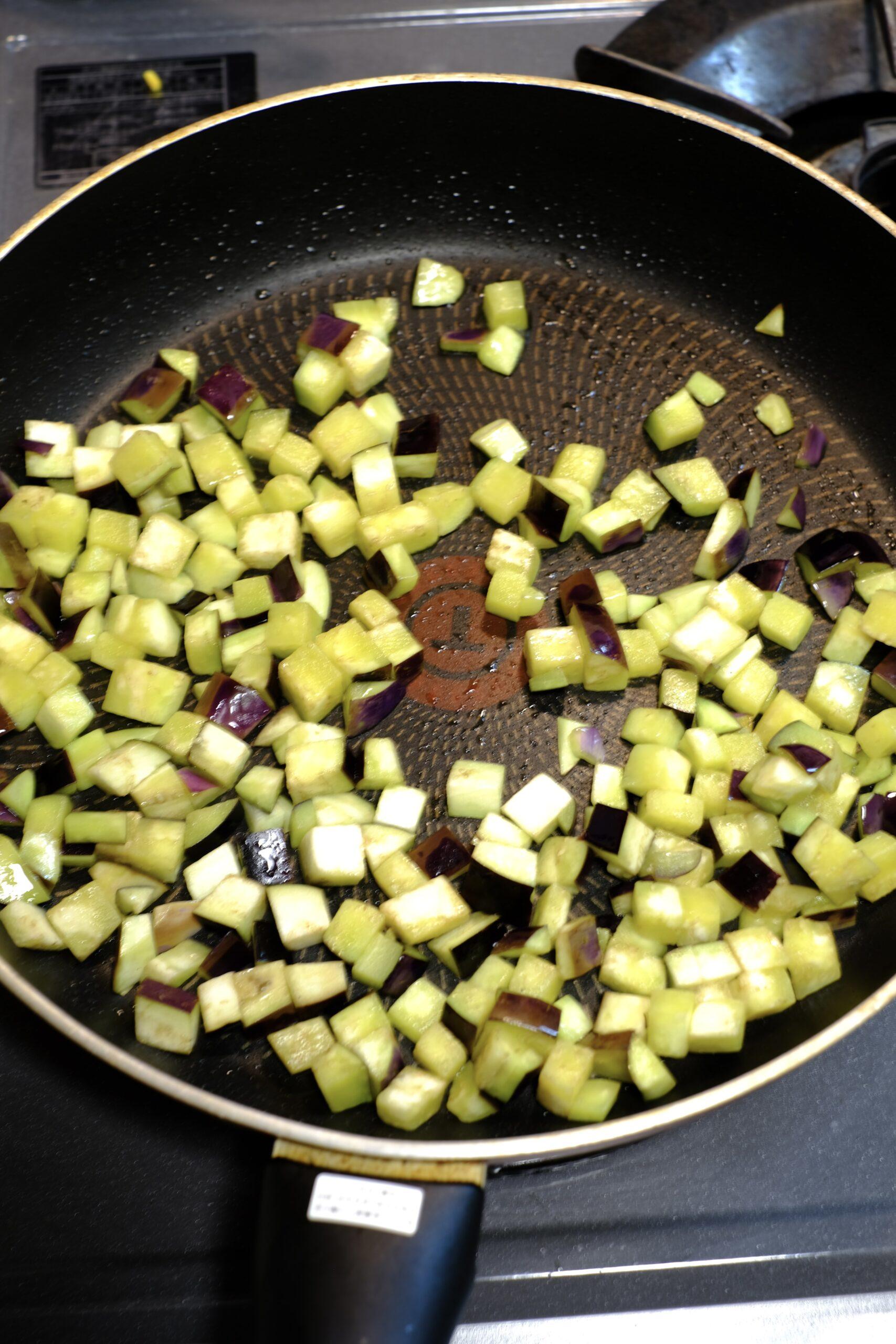 オリーブオイルをしっかり吸わせながら茄子を炒める様子の画像です