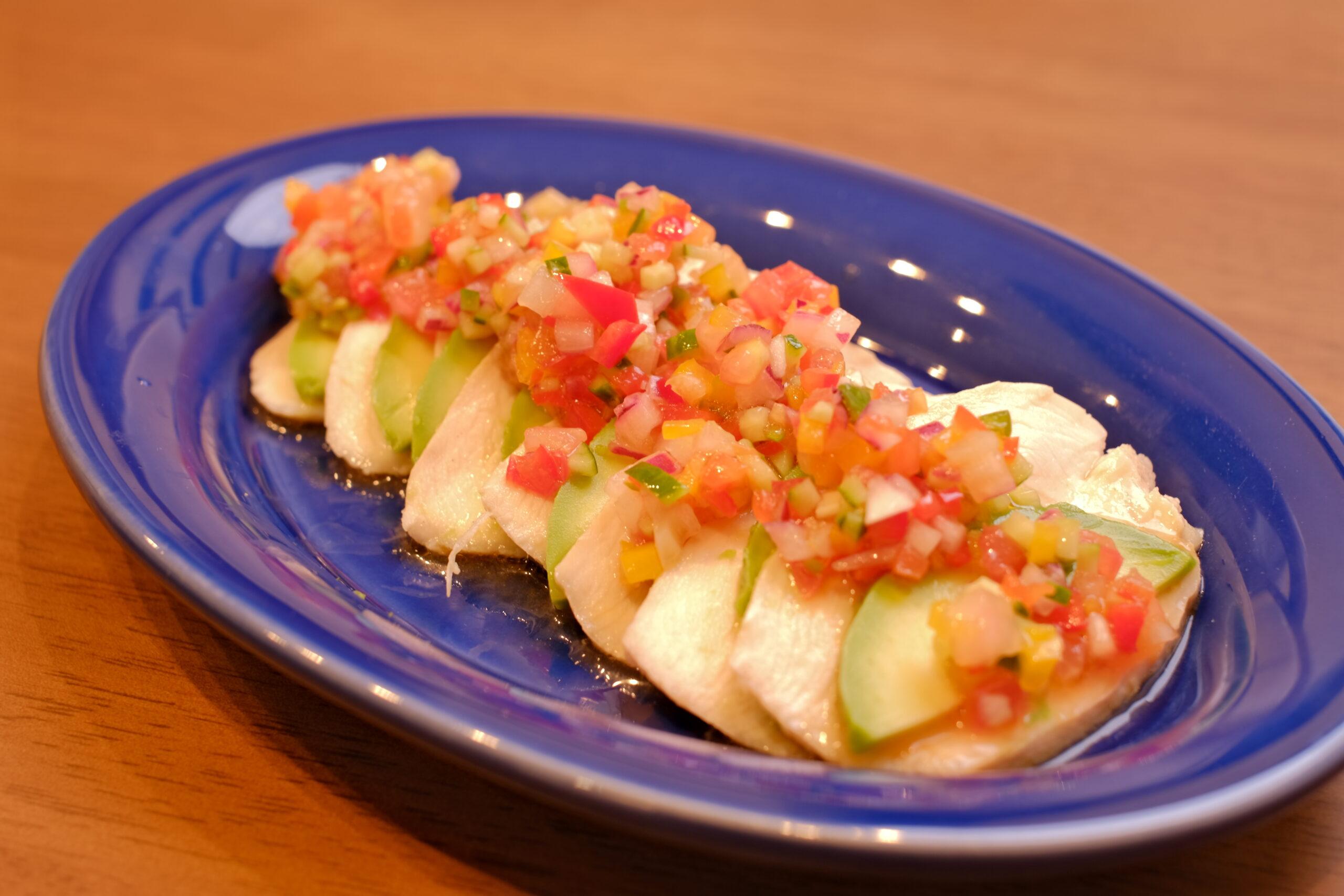 サラダチキンとアボカドのスライスに青唐辛子とたっぷり野菜のサルサソースをかけた料理の画像です